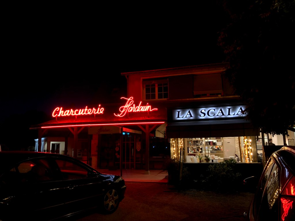 """Restaurant front with lit-up sign reading """"La Scala."""""""