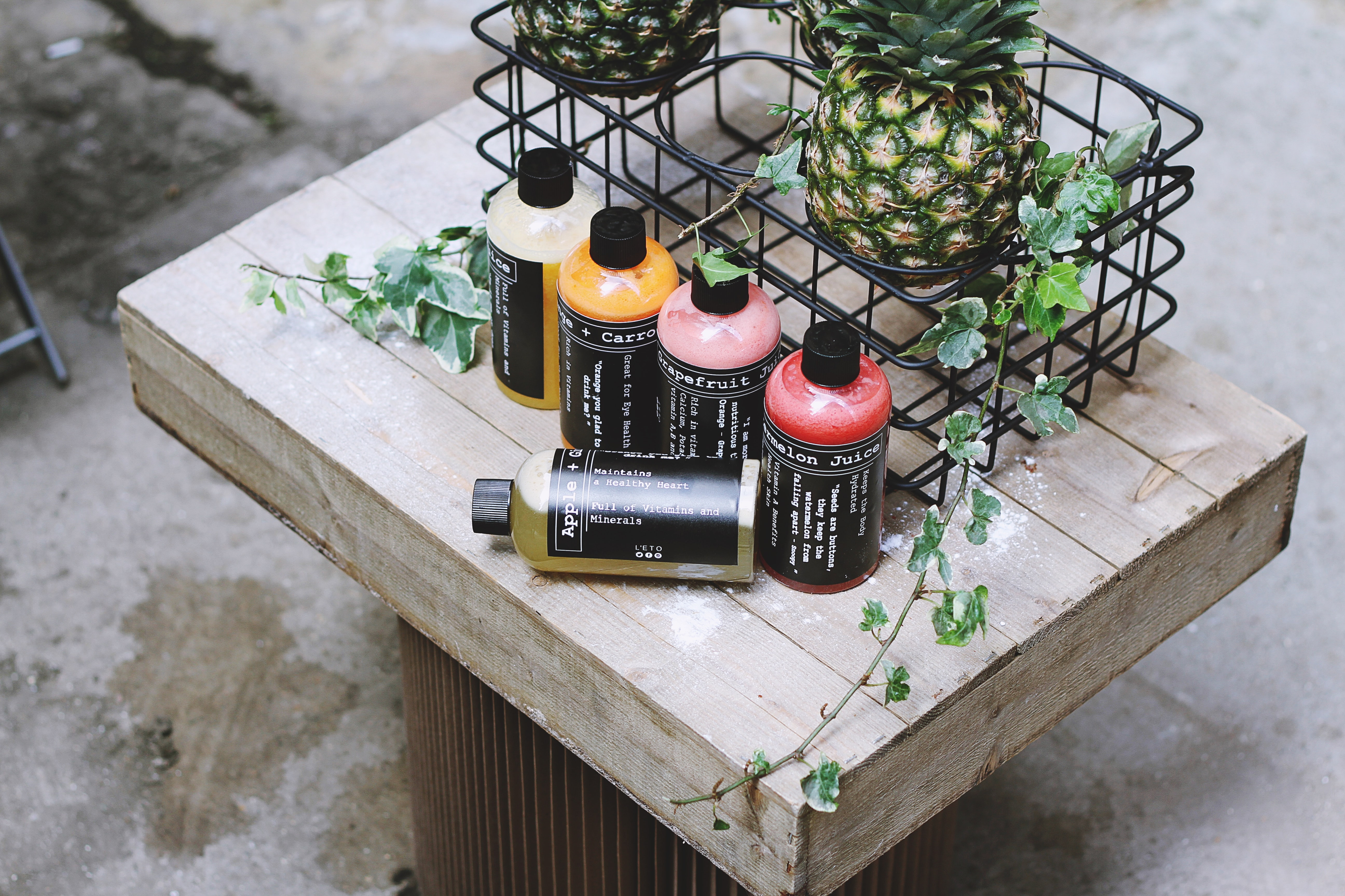 5 Shampoo Bottles on Wooden Table next to 2 Pineapples in a Black Cart