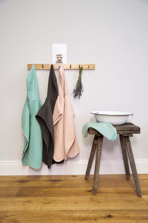 Drei hängende Badeponchos in den Farben mint, grau und rosa.