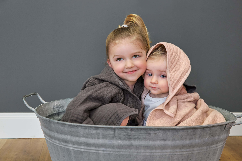 Zwei Mädchen mit farbigen Badeponchos.