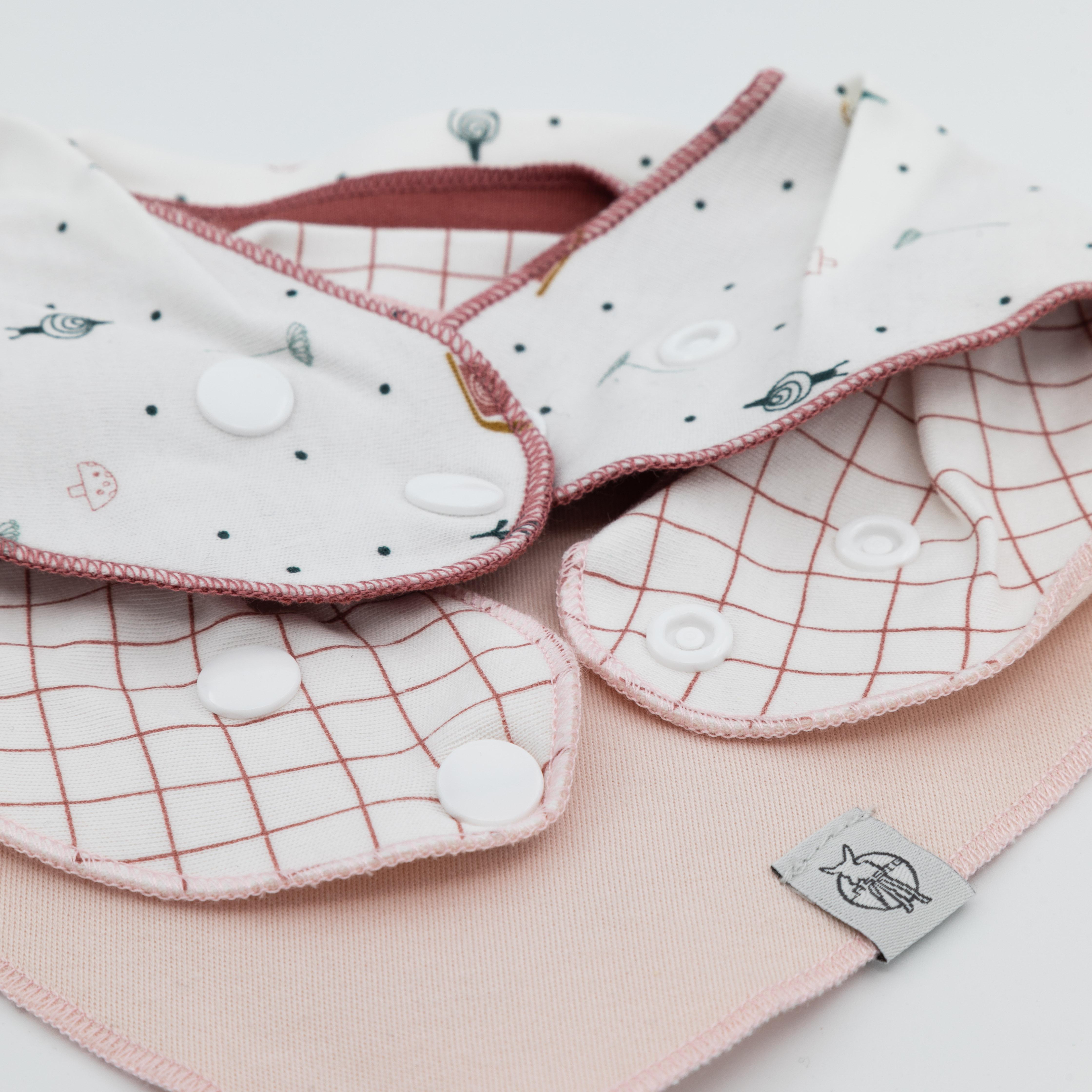Details Verschlussknöpfe von Dreieckstüchern in Rottönen.