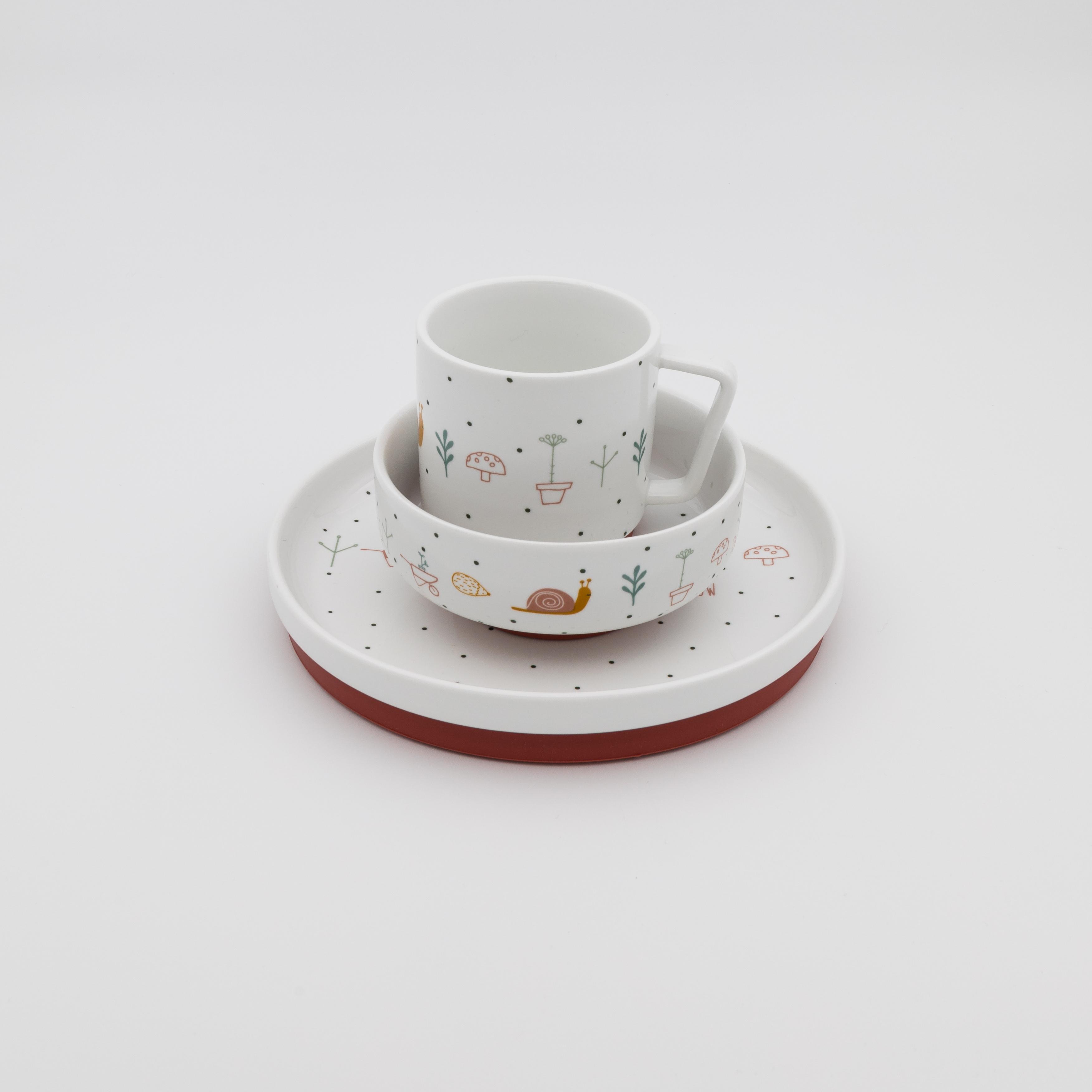 Weisses Kindergeschirr mit Gartenmotiven bestehend aus Teller, Müslischale und Tasse.
