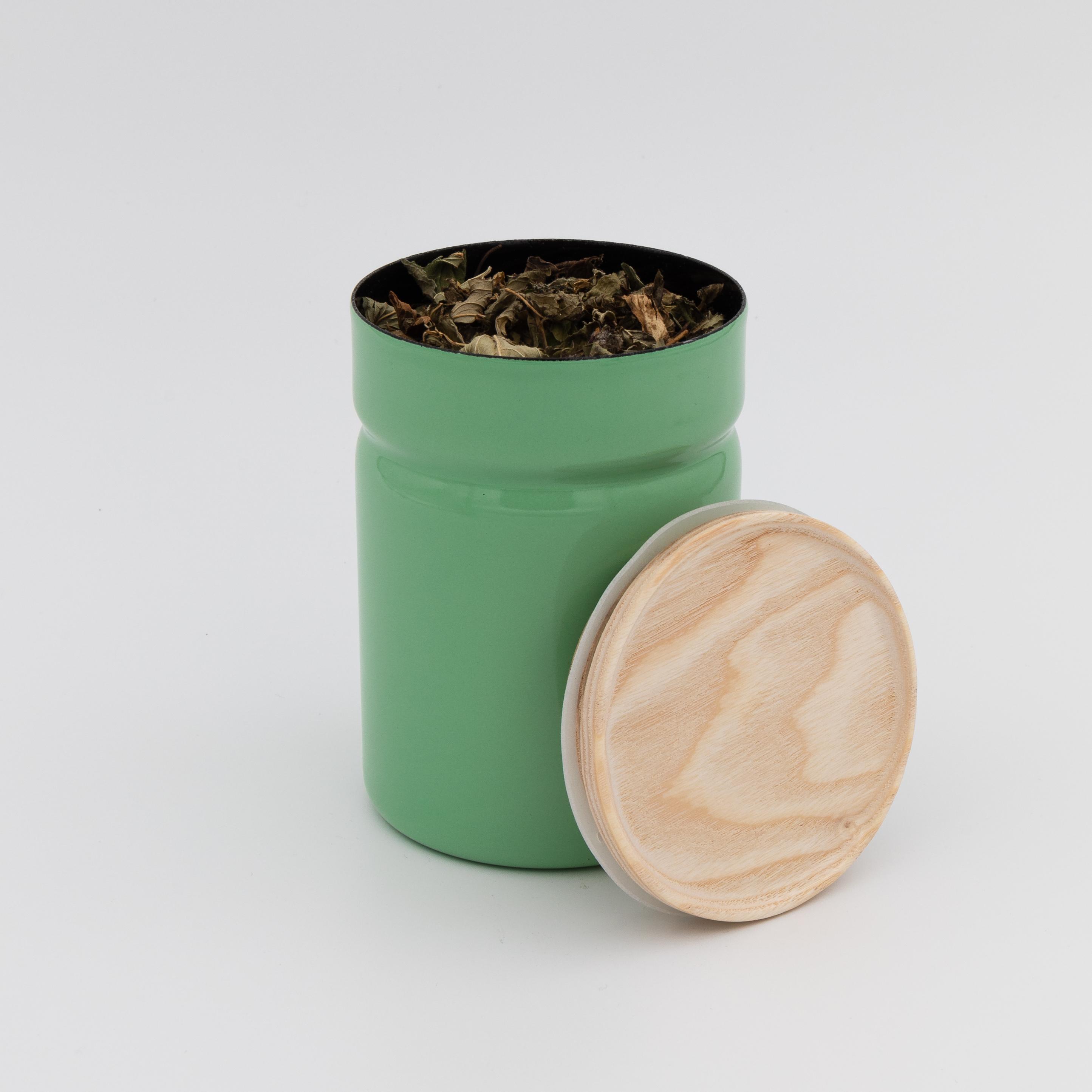 Hellgrüne Vorratsdose geöffnet mit Holzdeckel.