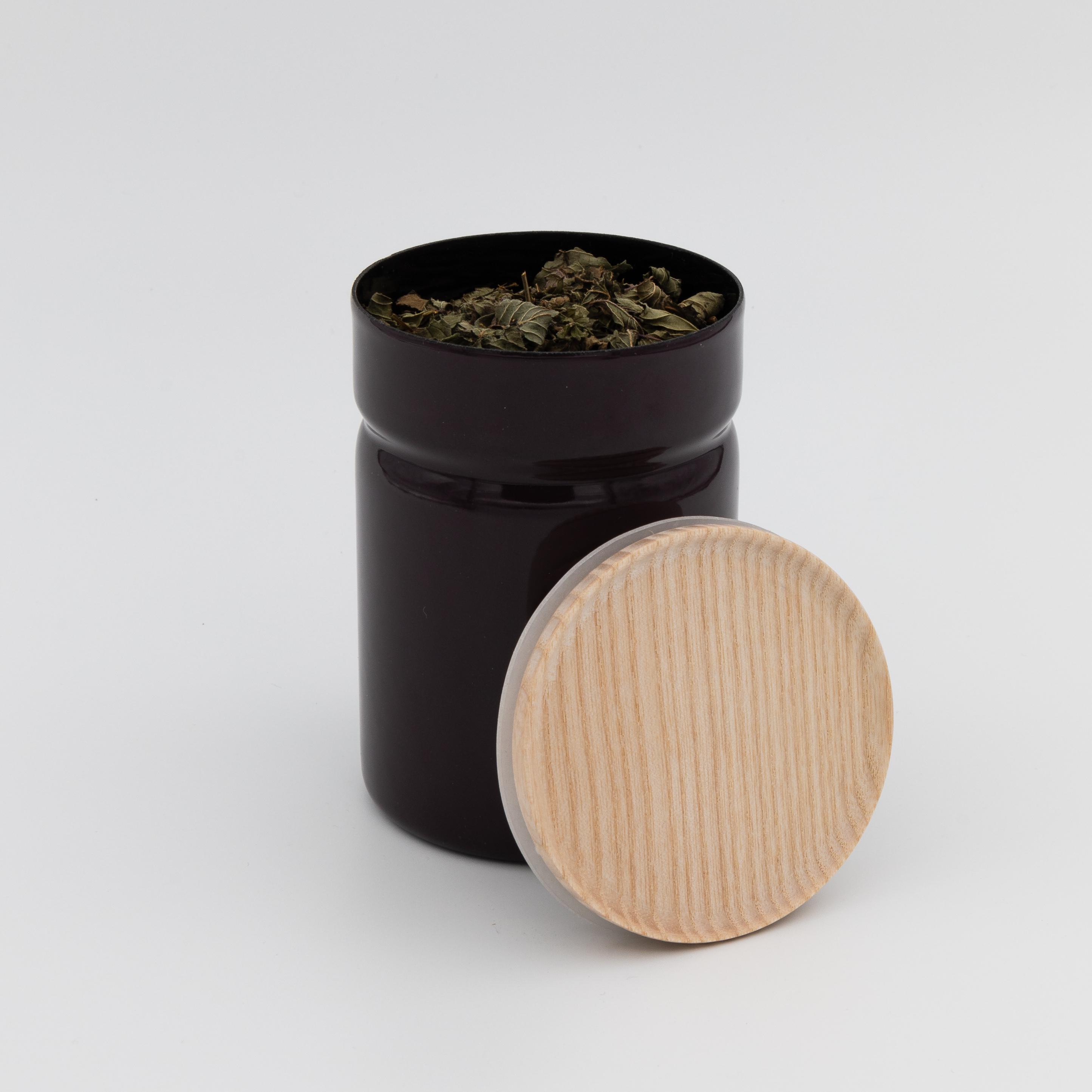 Geöffnete Vorratsdose in der Farbe Aubergine mit Holzdeckel.