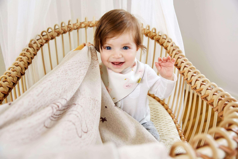Kleinkind mit Decke in der Hand und Dreieckstuch mit Schwanmotiv um den Hals.