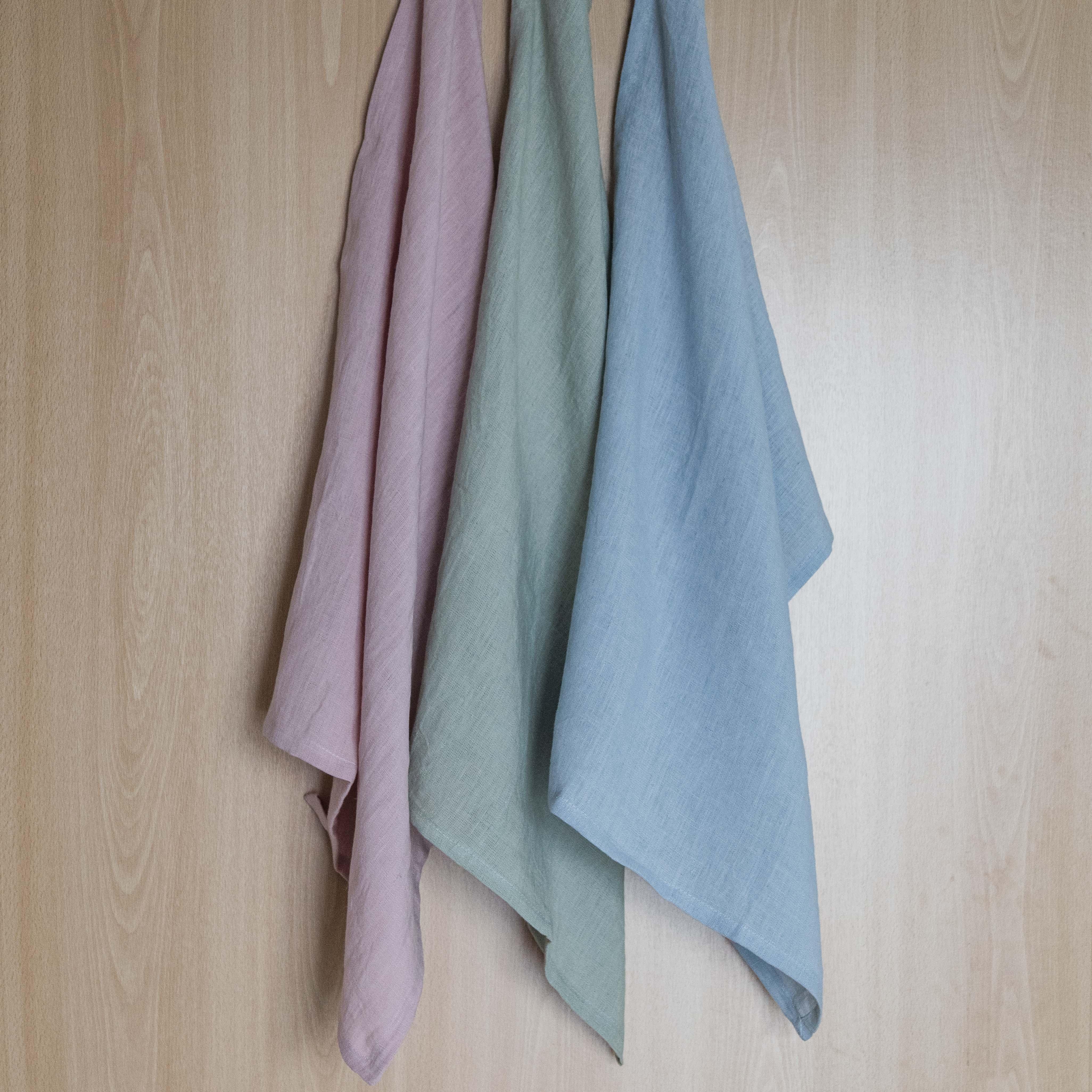 Drei hängende Geschirrtücher in den Farben rosa, grün und blau.