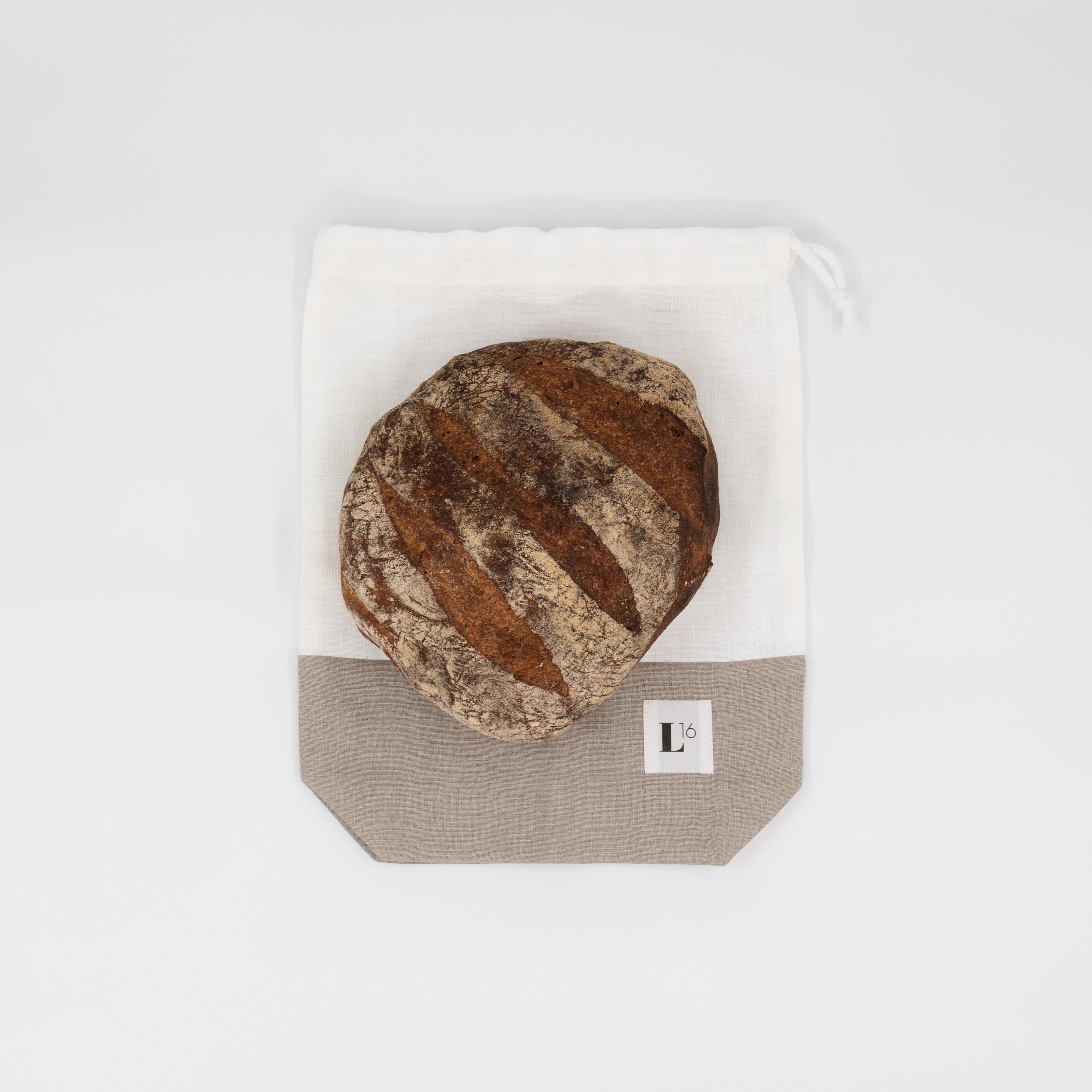 Leinensack in weiss/grau mit Brot drauf.
