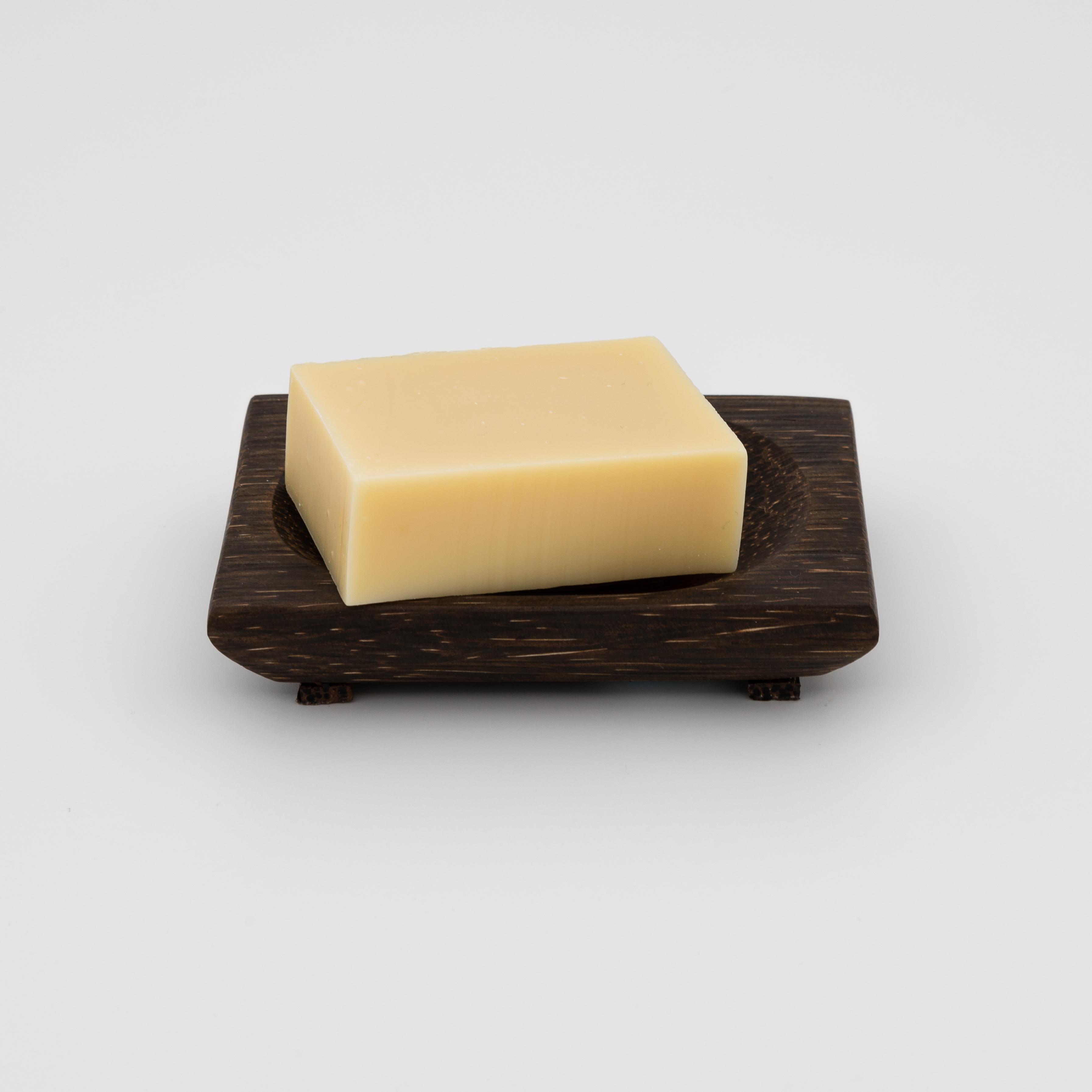 Seifenschale aus dunklem Holz mit Seife drin.