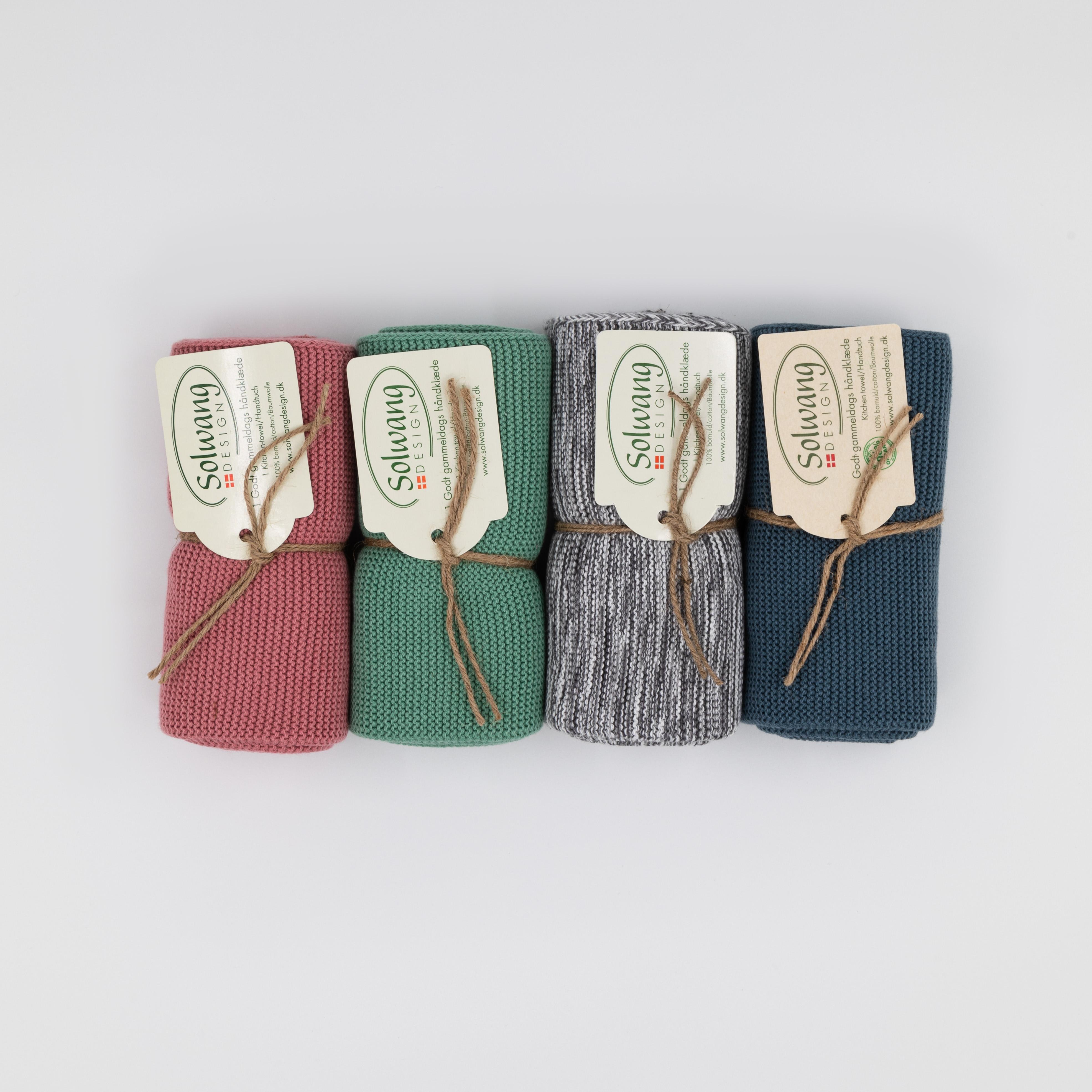 Zusammengerollte Handtücher in den Farben altrosa, grün, grau und dunkelblau.
