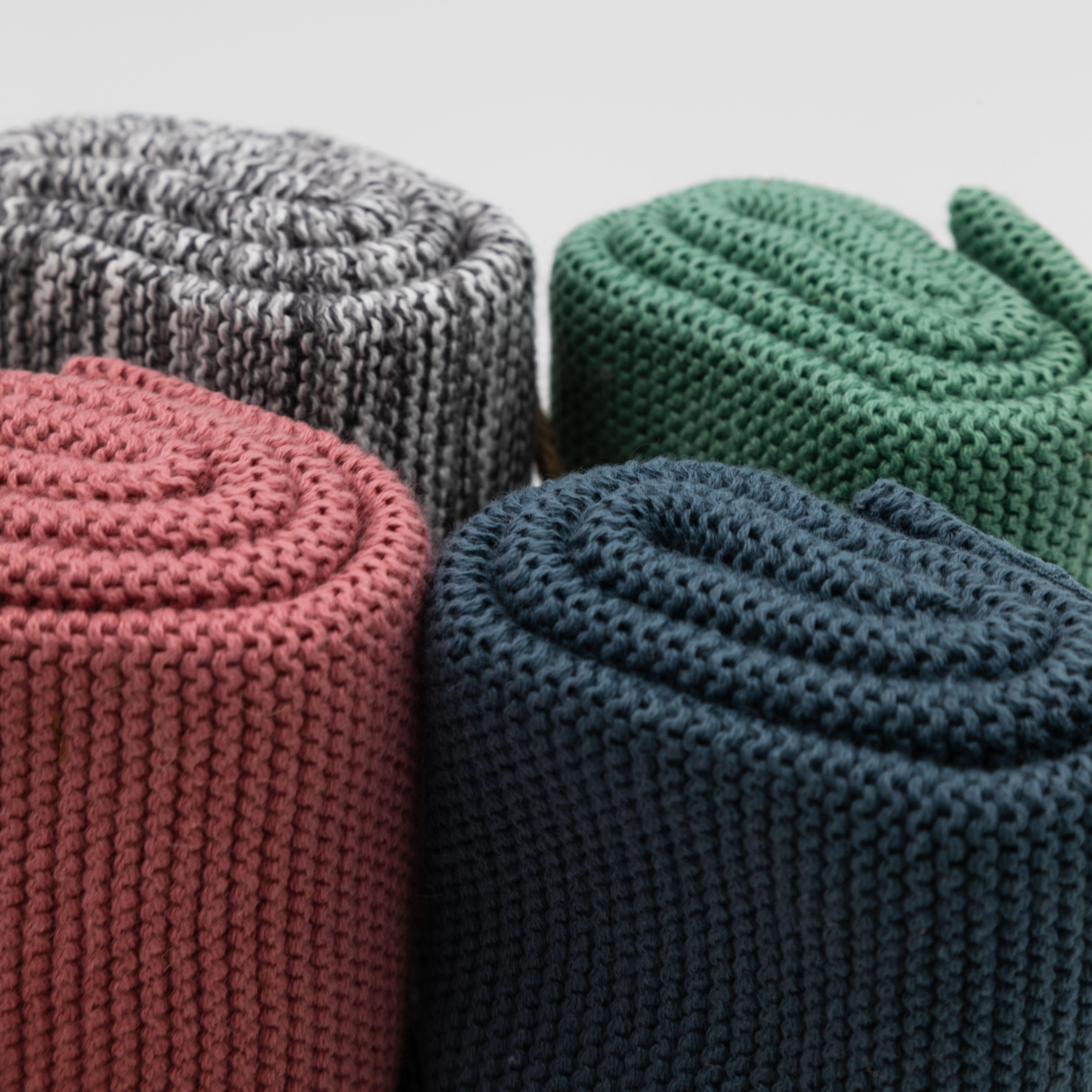 Detailaufnahme von zusammengerollten Handtüchern in grau, altrosa, grün und dunkelblau.