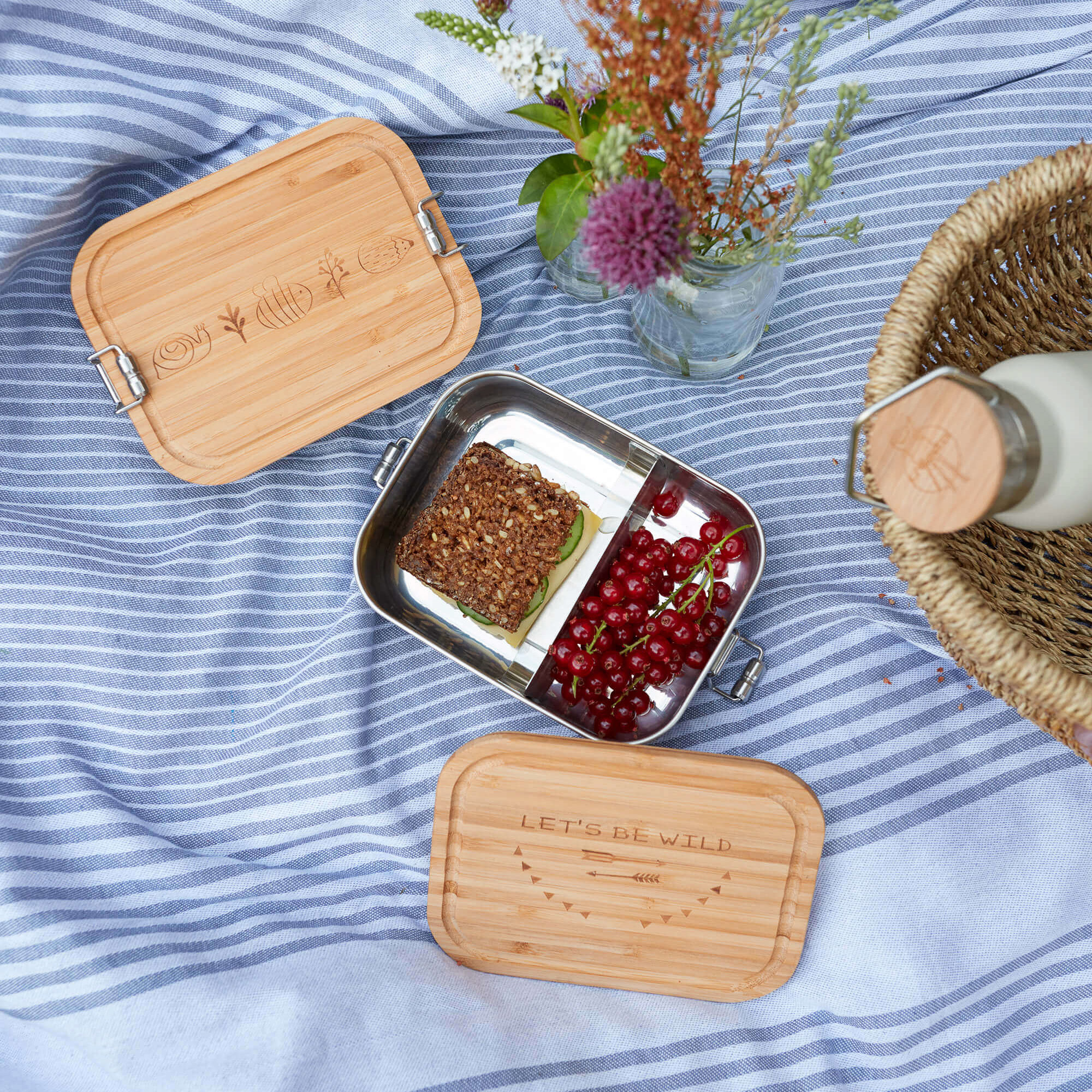 Lunchbox aus Edelstahl mit Bambusdeckel auf blauer Picknickdecke.