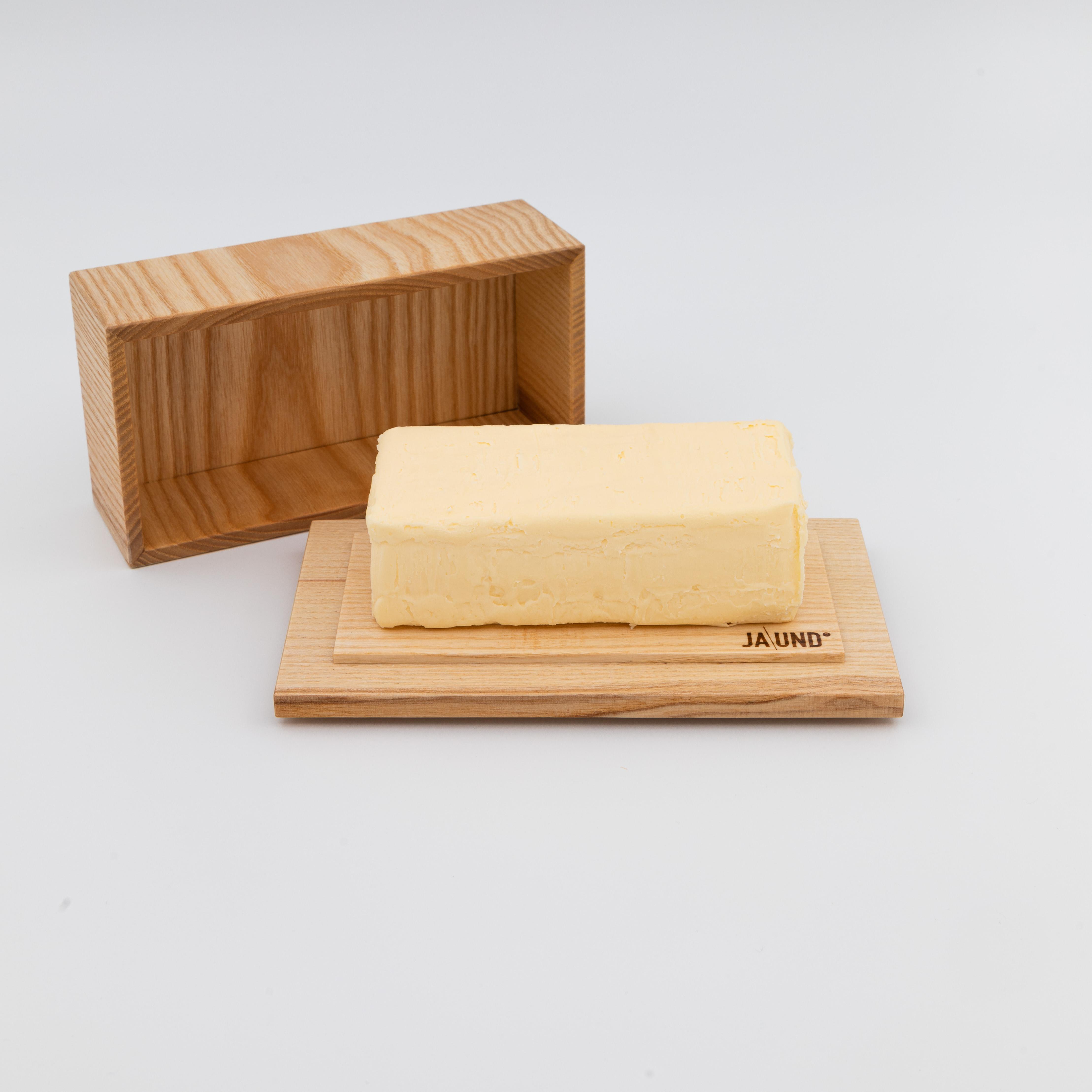 Butterbox aus hellem Holz mit offenem Deckel und Butter drauf.