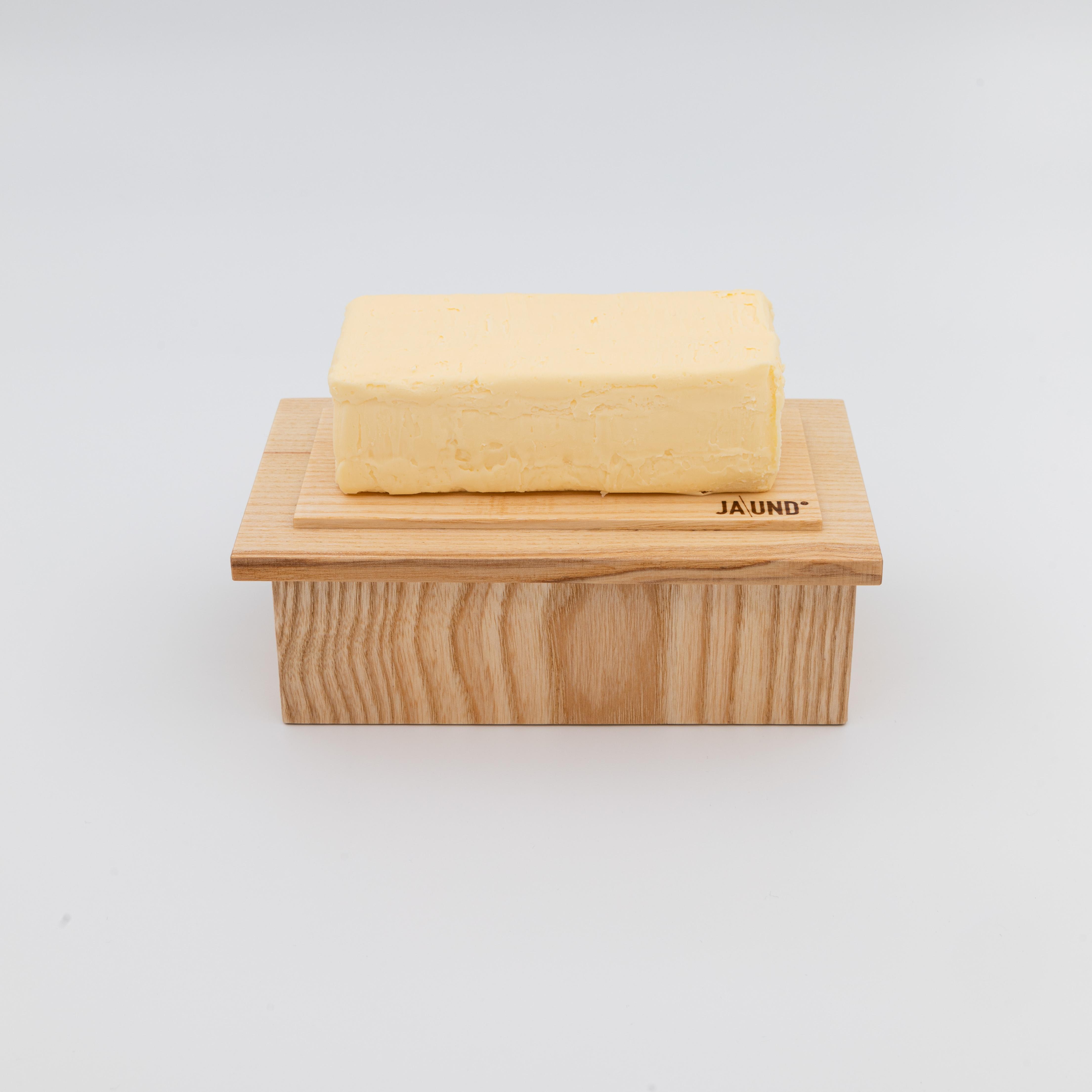 Butterbox aus hellem Holz mit Butter drauf.