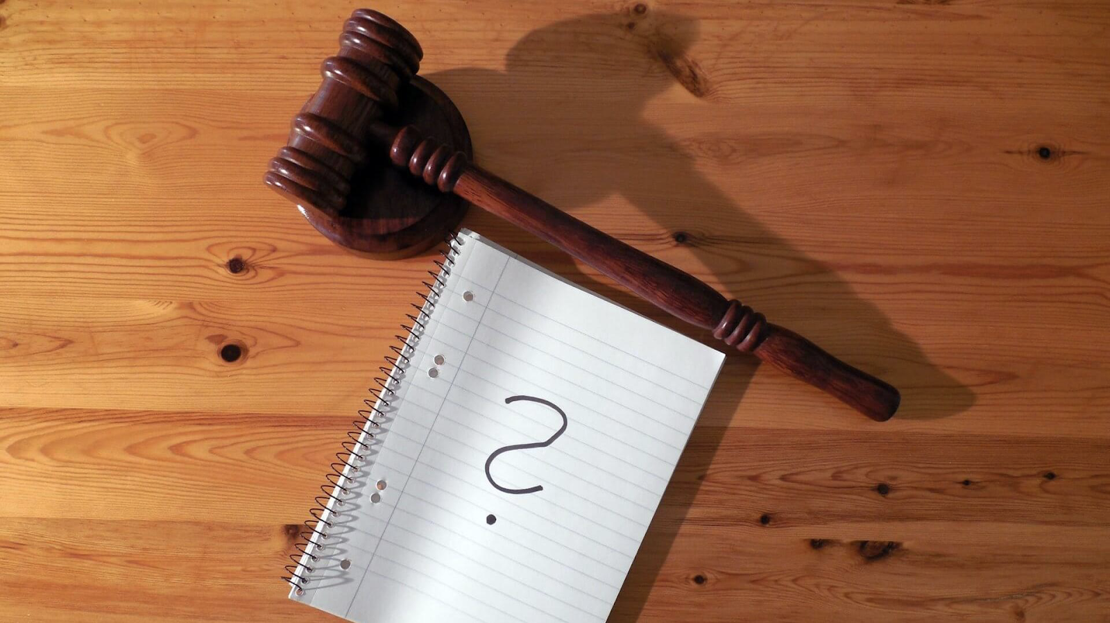 Notebook with question mark about unresolved case and a wooden gavel on the wooden table