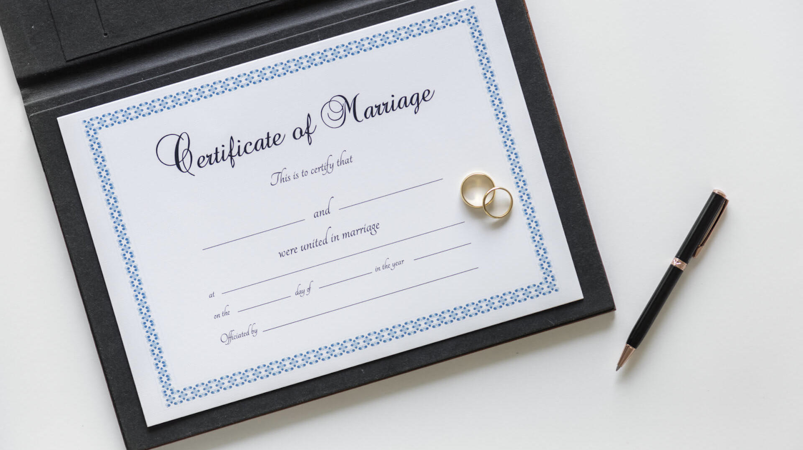 Marriage certificate, two rings and a pen on white table
