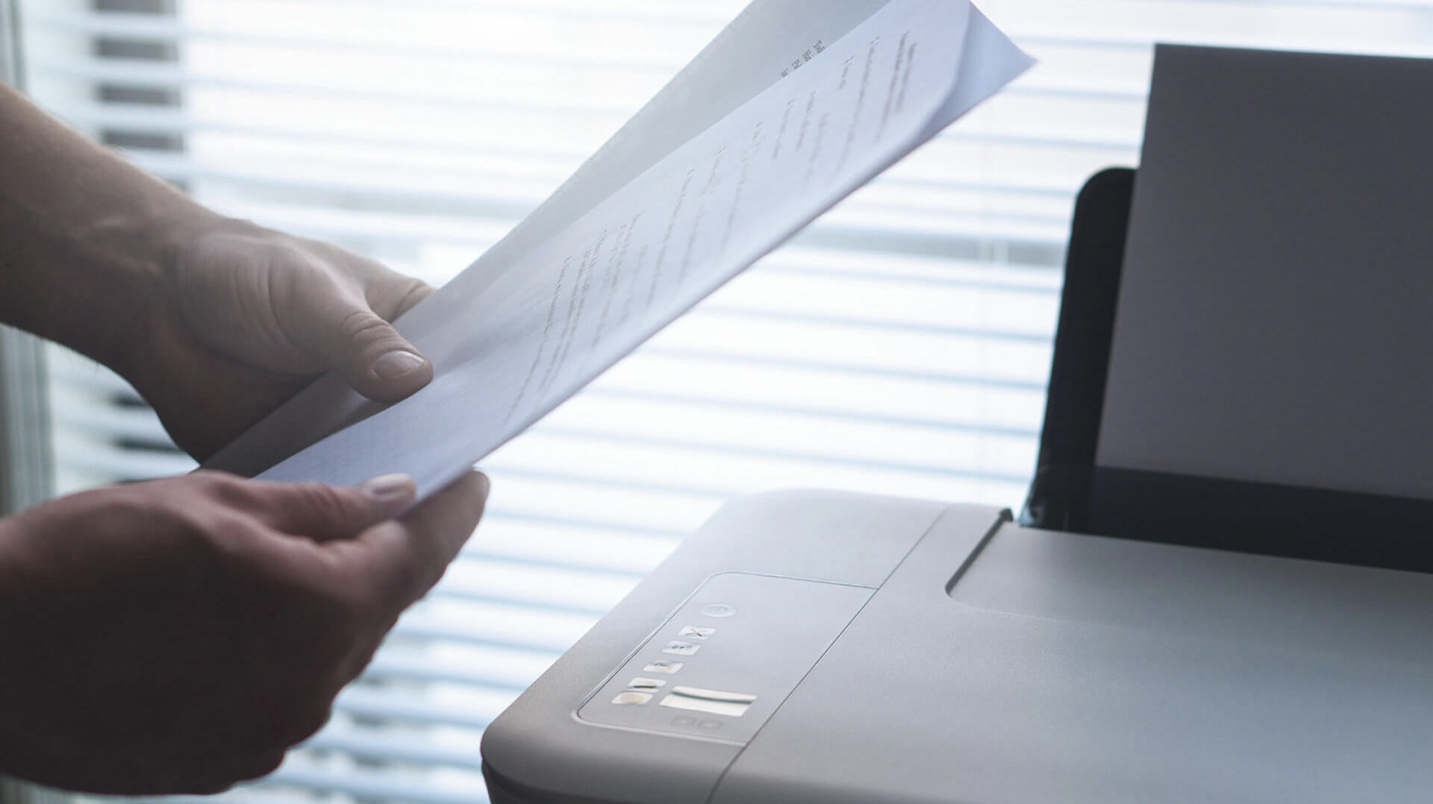 Hands holding documents near the printer and a large window