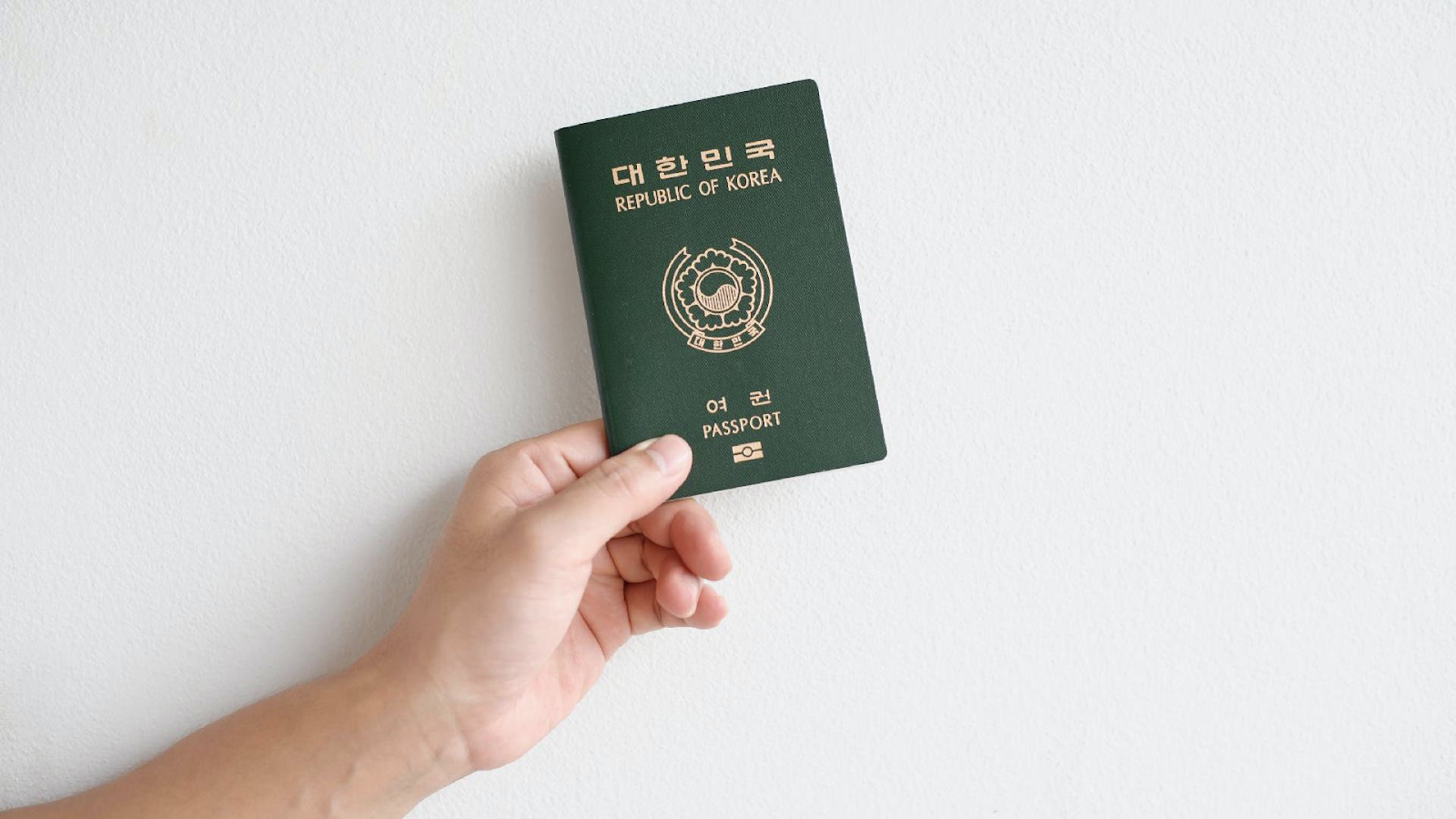 Hand holding passport of the Republic of Korea on white background