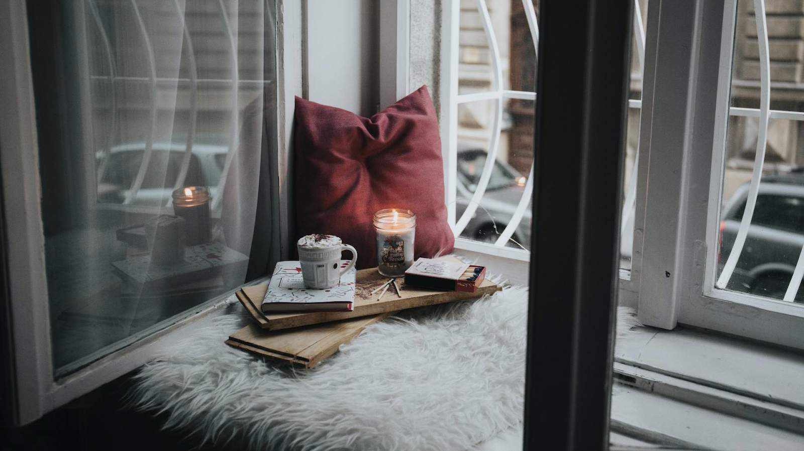 cozy window seating with books, candle and hot chocolate at home