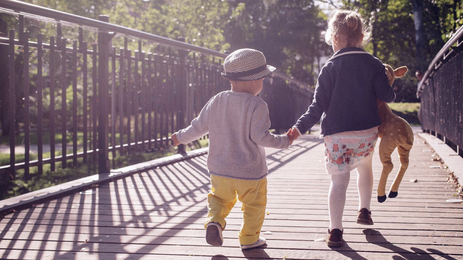 Infant boy and little girl holding hands and walking in the park