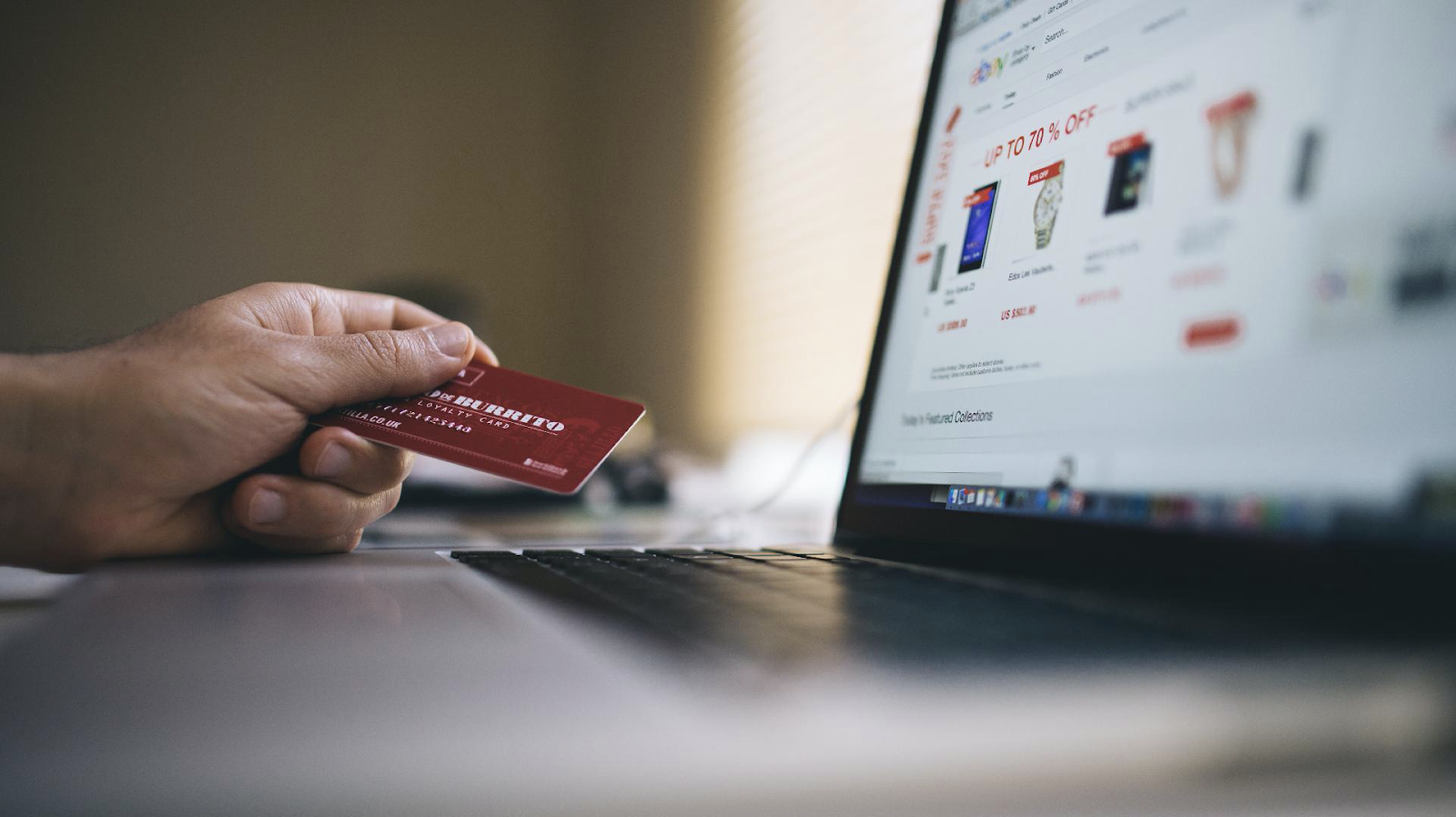 Hand holding credit card in front of a laptop doing some purchases in online shopping.