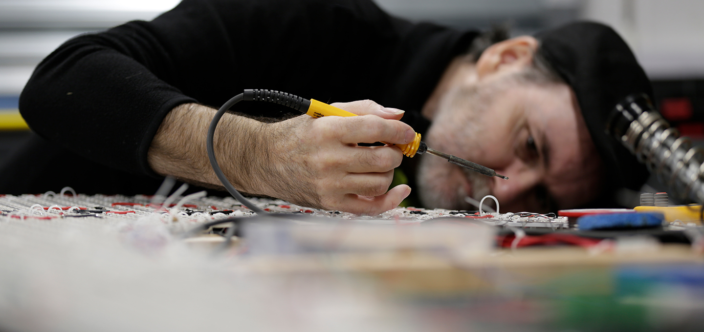 A technician soldering electrical signage