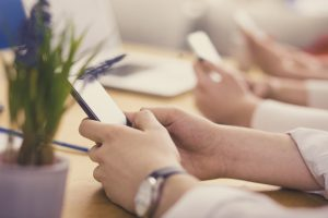 Young casual business people using smart phone for social networking
