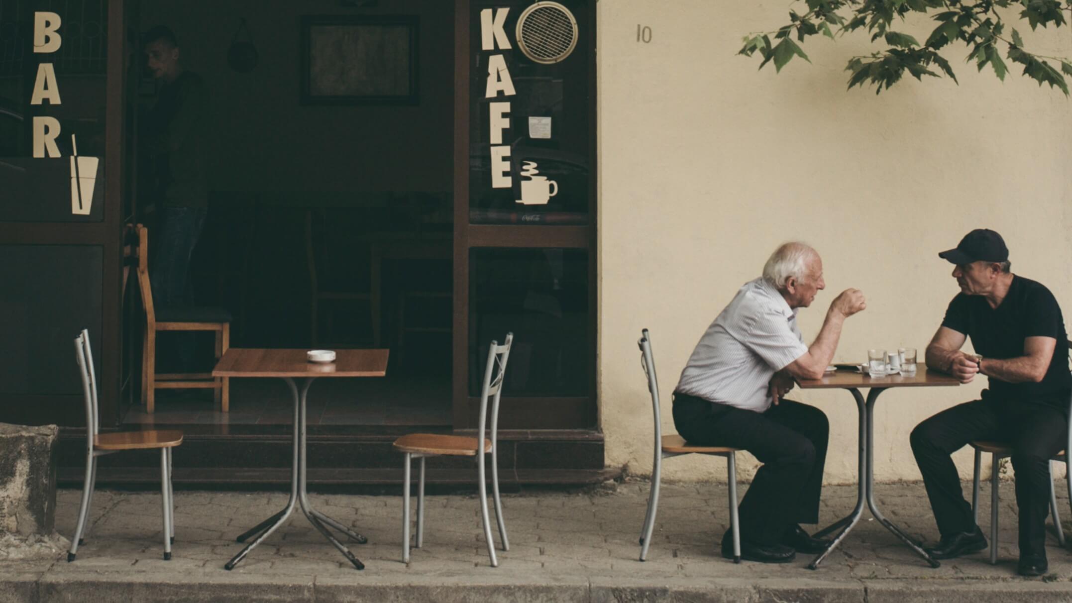 Dois homens conversando em um café