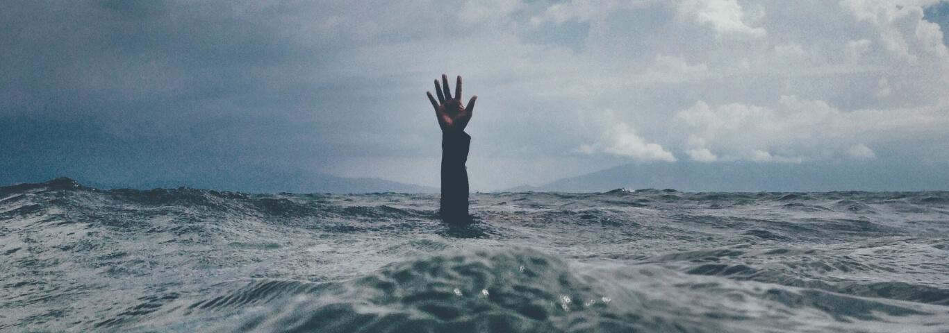 Braço estendido para fora da água do mar