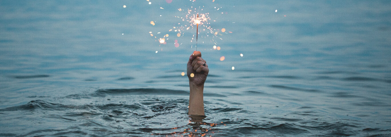Pessoa submersa na água segurando uma vela com faíscas