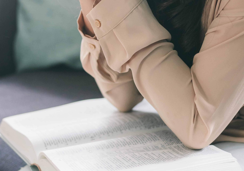 Junge Frau betet mit Bibel