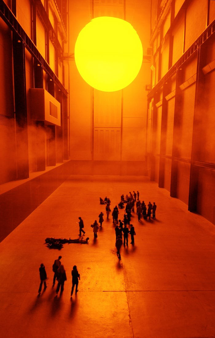 Illuminating sun resting atop the museum's ceiling with visitors admiring from above
