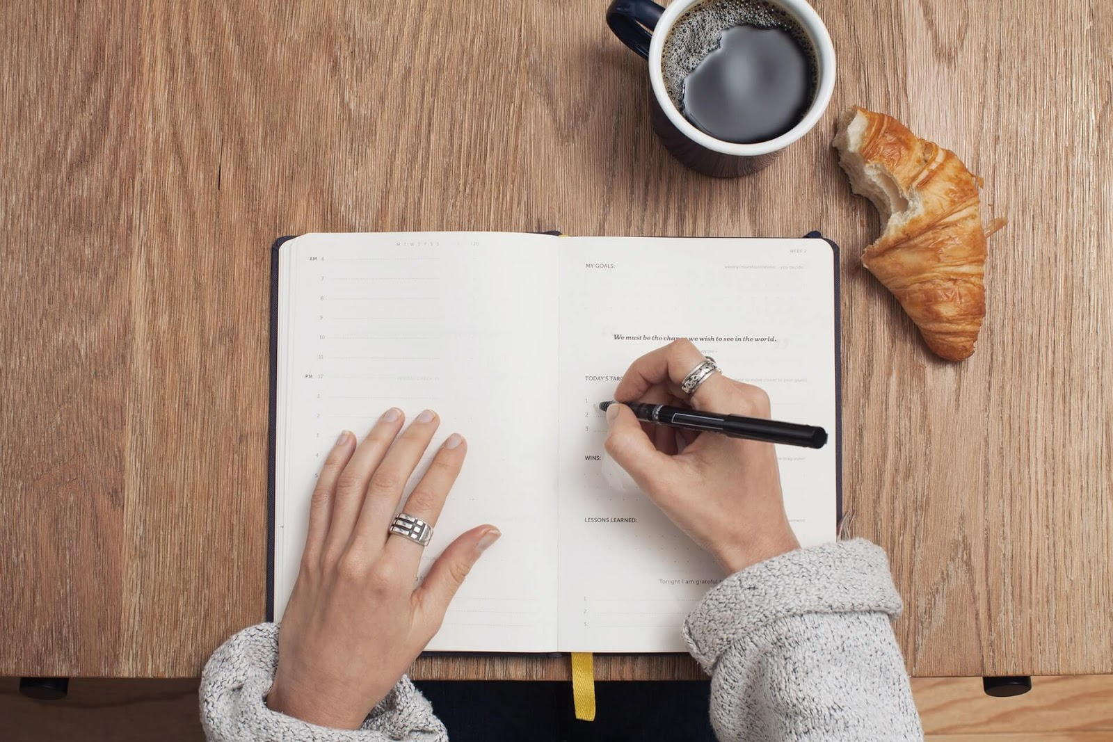 person writing in a notebook with coffee and bun on the table