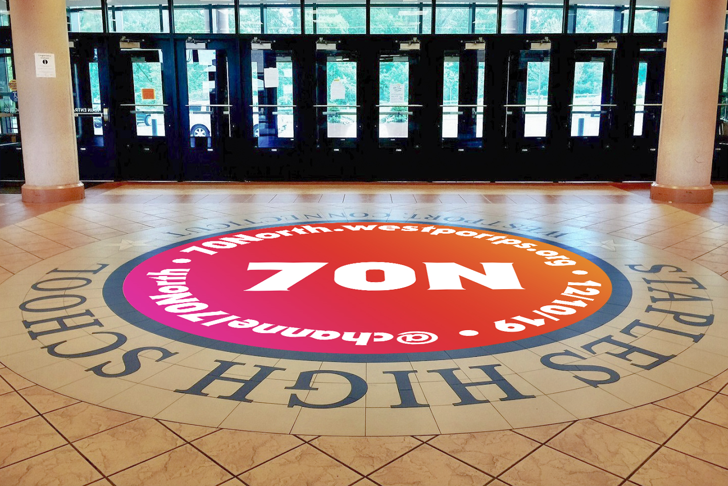 A conceptual lobby floor decal featuring the 70 North logo, the December 5th launch date, and the URL.
