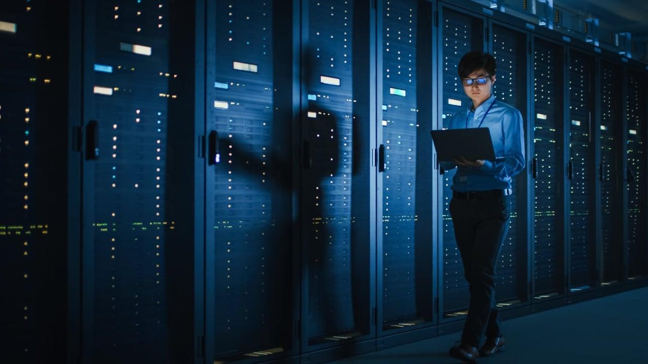 Segurança da Informação e de dados. Técnico de etnia oriental caminha por servidores data center realizando monitoramento