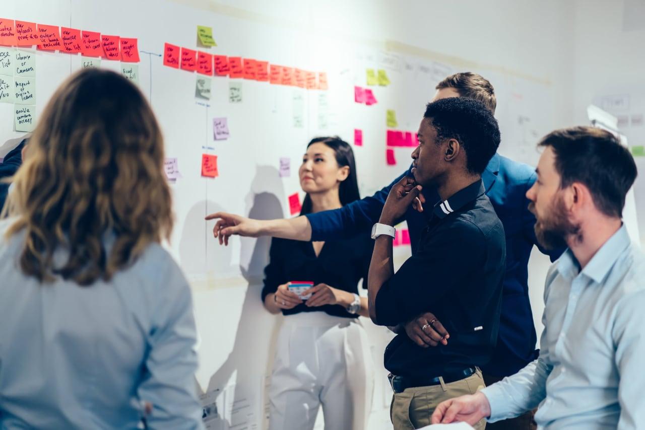 Equipe multicultural discute projetos de TI  olhando para board