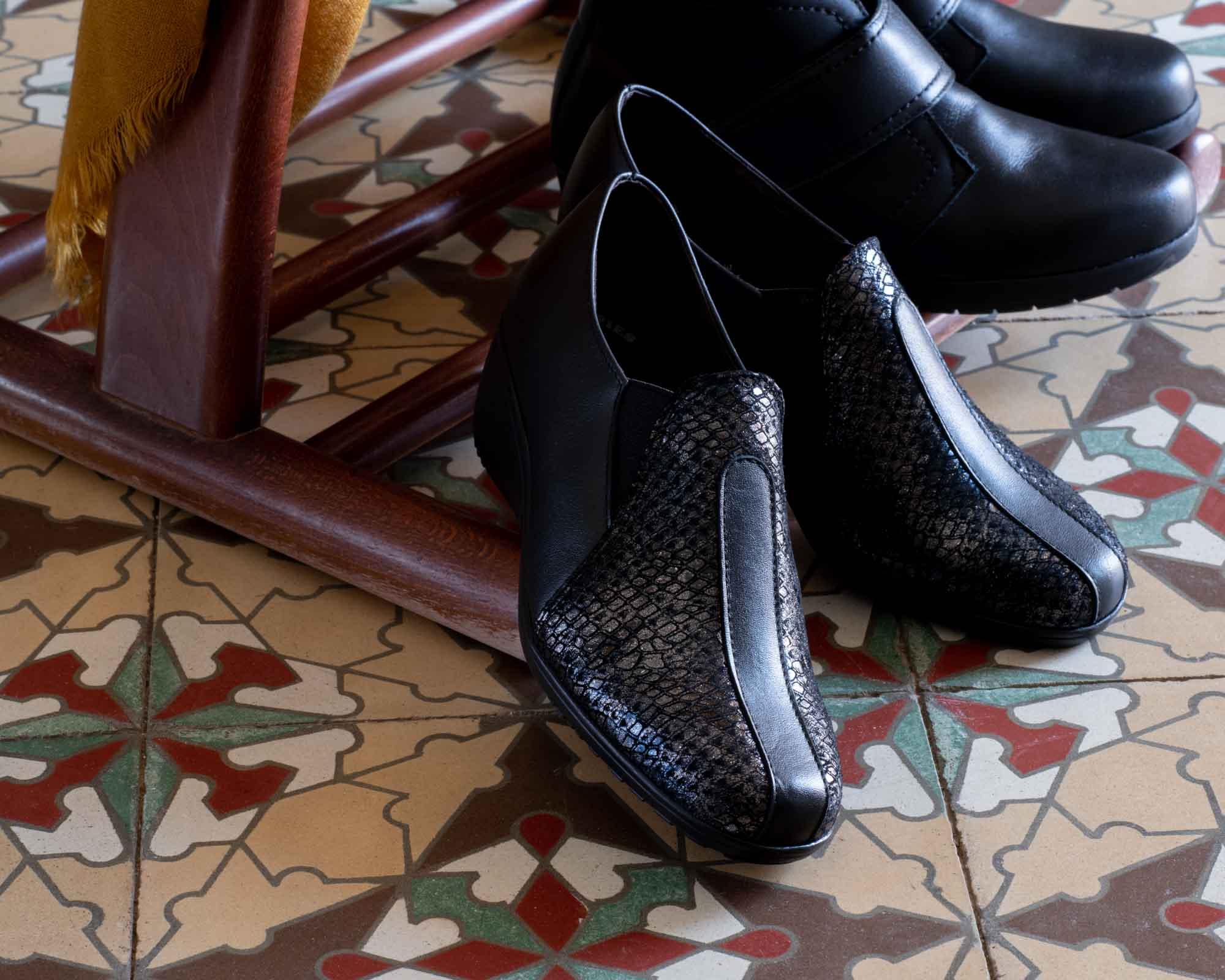 Dos pares de zapatos de otoño oscuro sobre baldosas marrones español