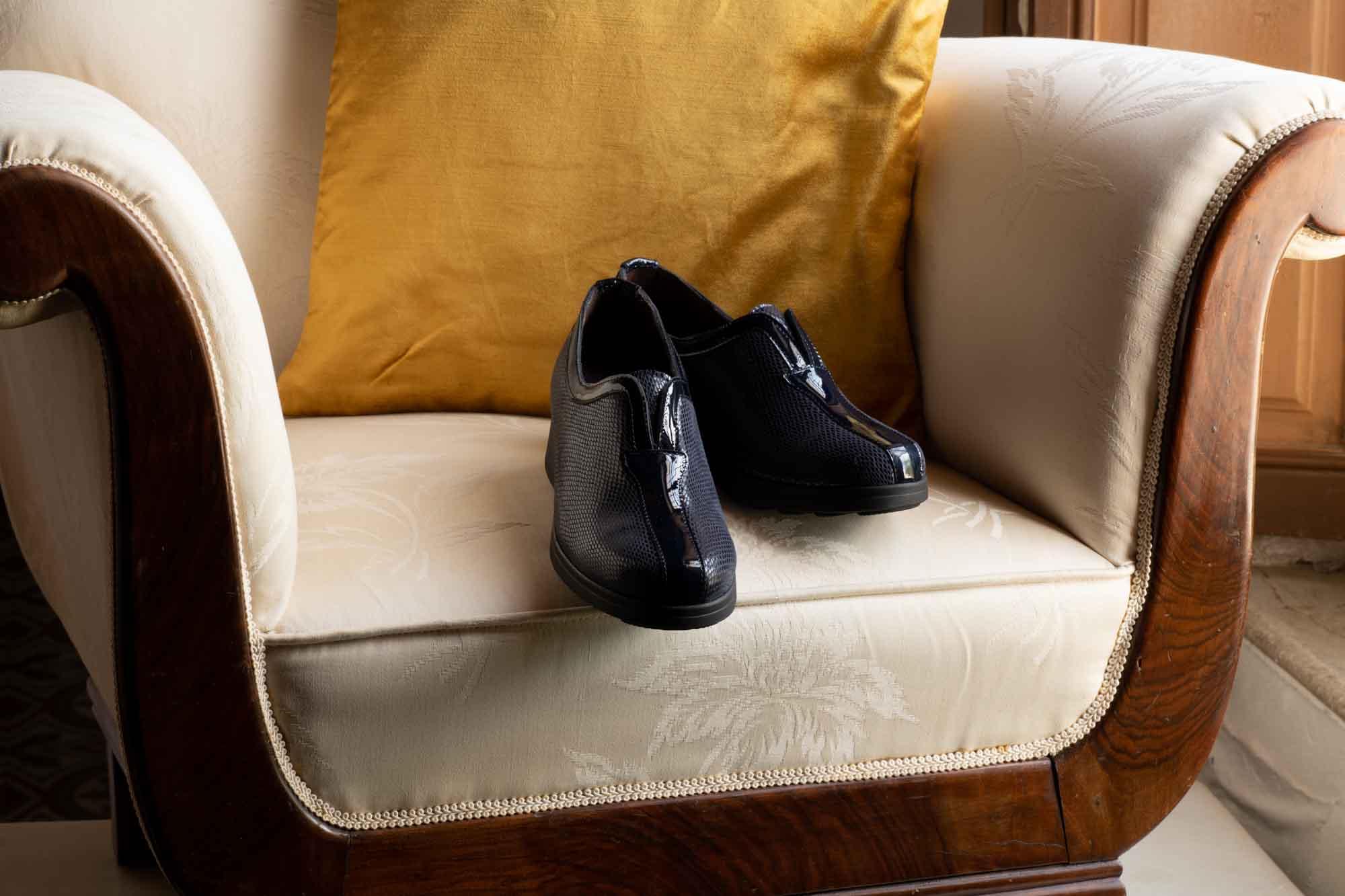 Zapatos azul oscuro en silla antigua de color claro y cojín naranja