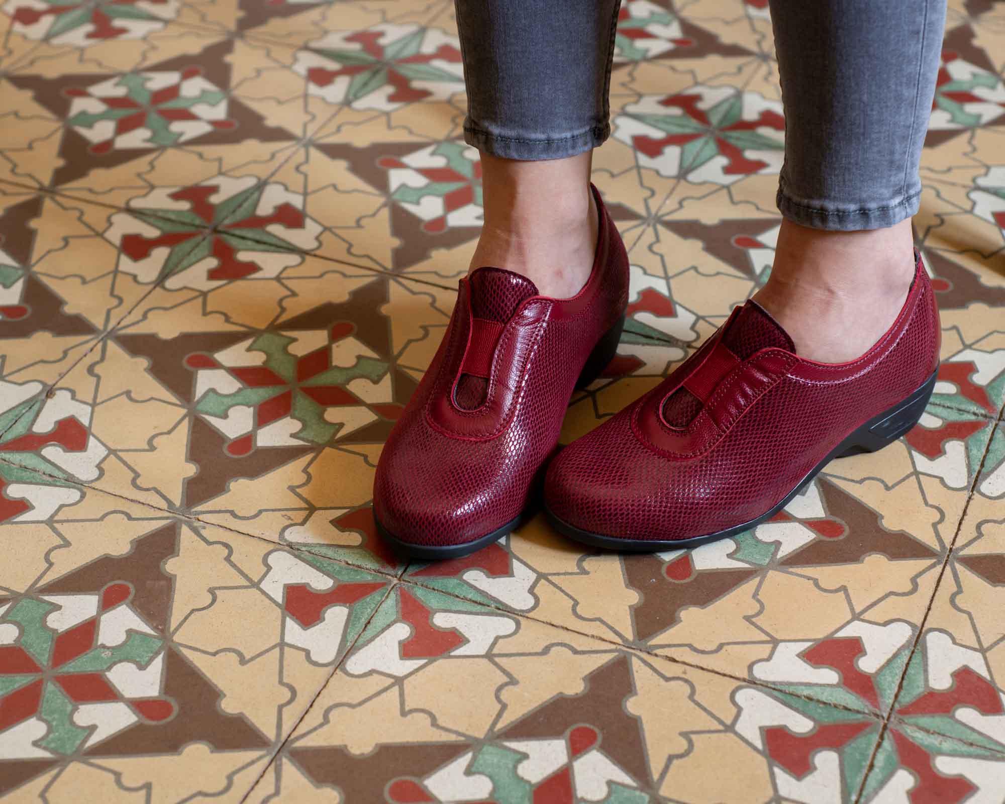 Piernas de mujer con zapatos rojos, con baldosas marrones españoles
