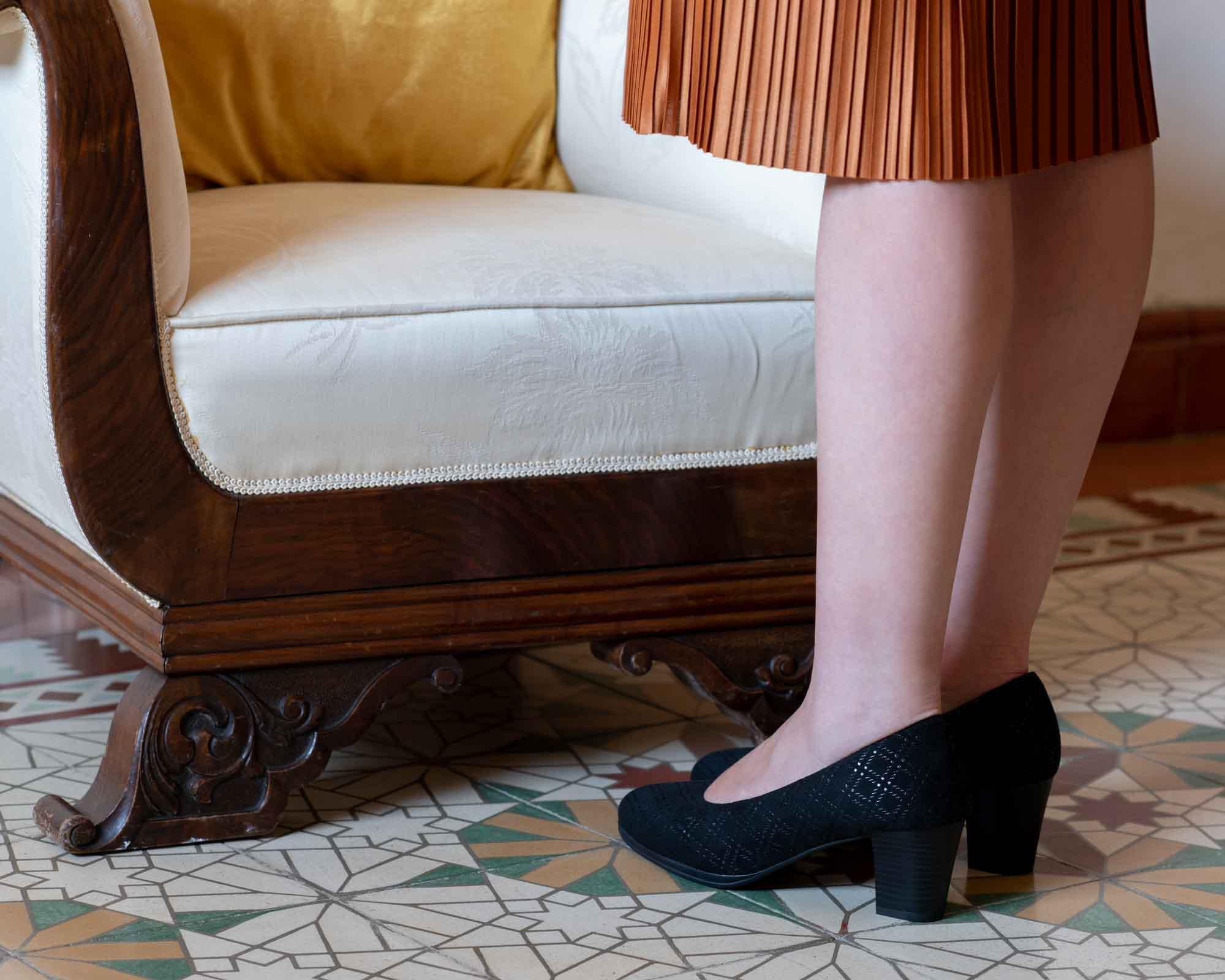 Mujer de pie junto a la silla antigua con tacones negros y vestido naranja con baldosas españolas.
