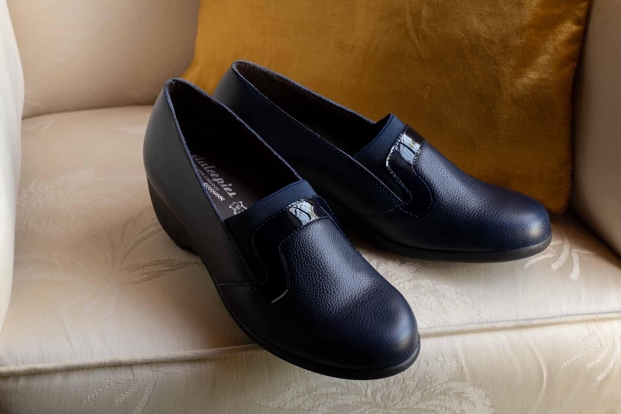 Zapatos azul oscuro en silla antigua de color crema