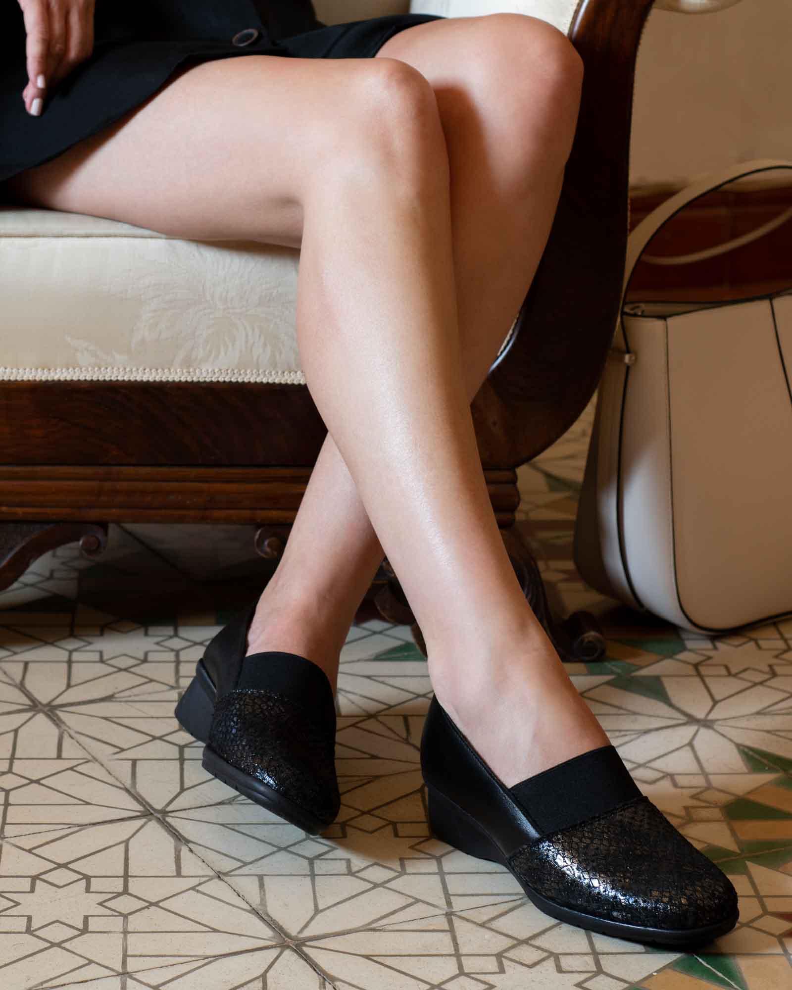 Mujer sentada en una silla antigua con zapatos negros y vestido con baldosas españoles.