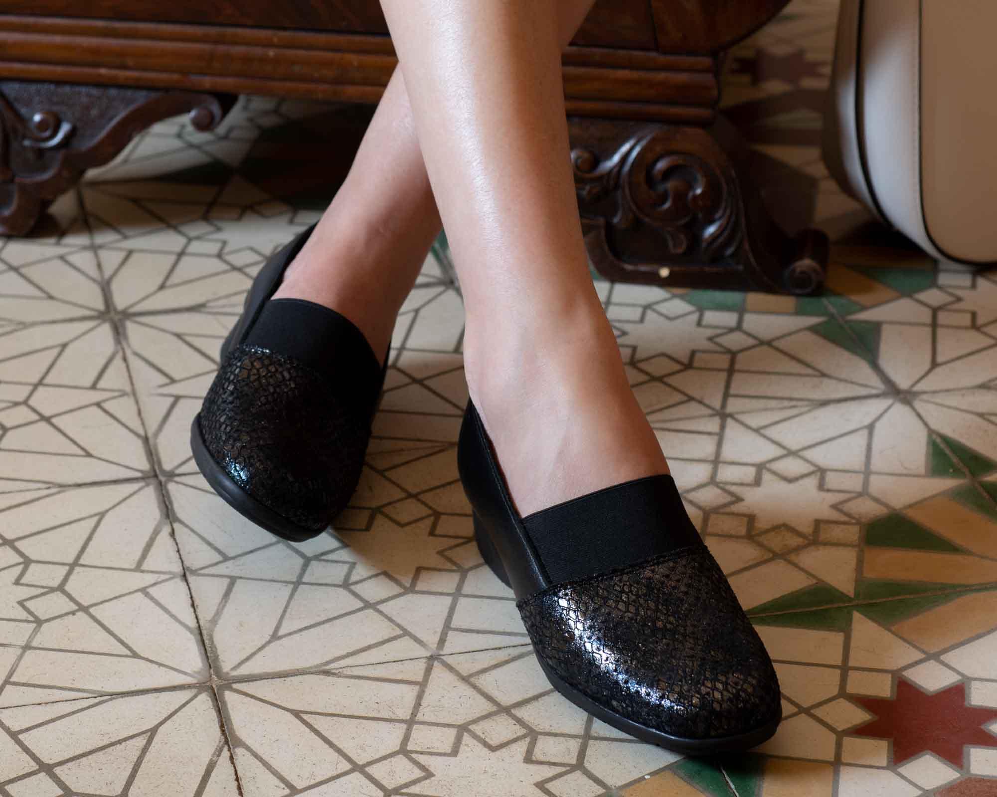 Piernas de mujer con zapatos negros elegantes, con baldosas marrones españoles