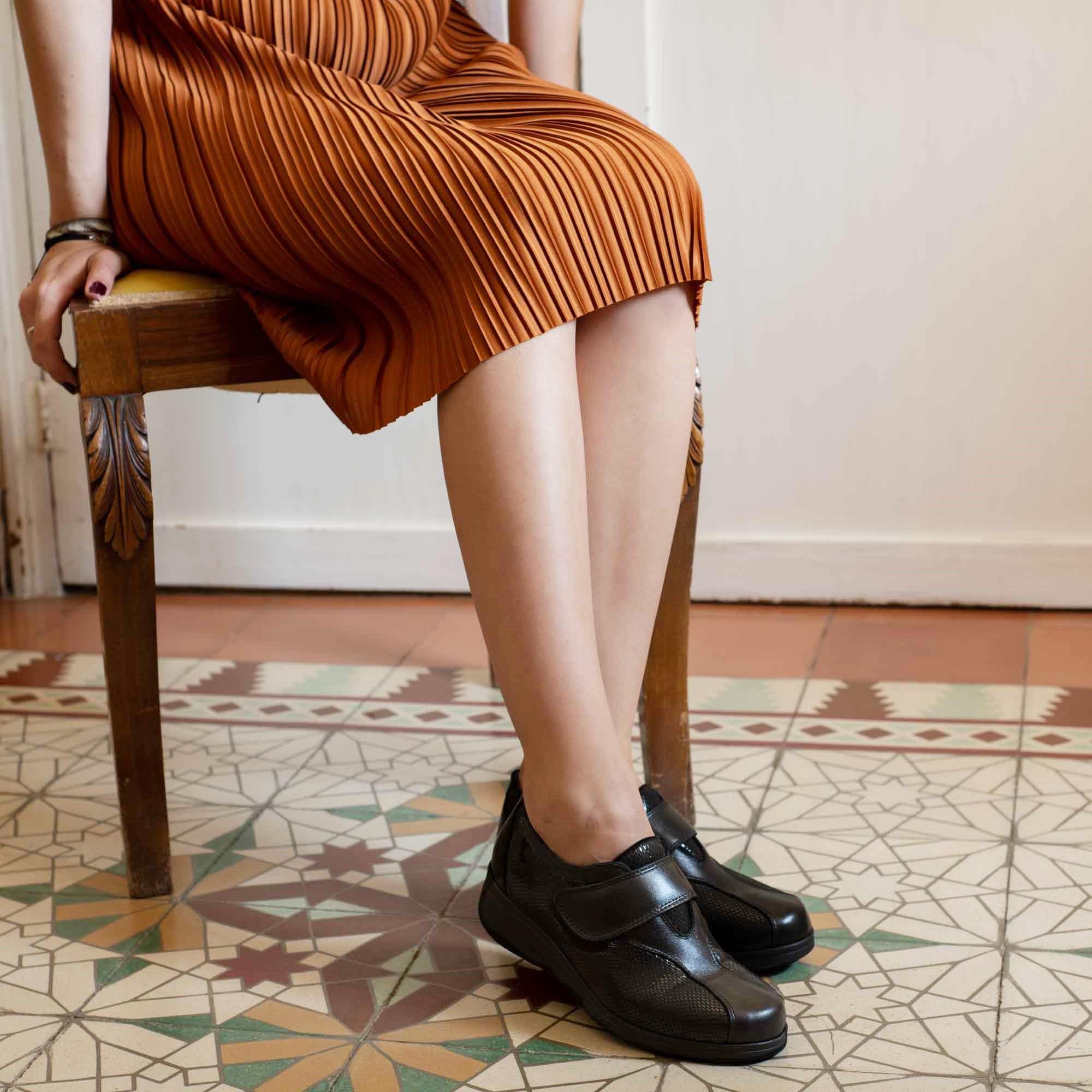 Piernas de mujer con vestido naranja y zapatos negros, con baldosas marrones españoles