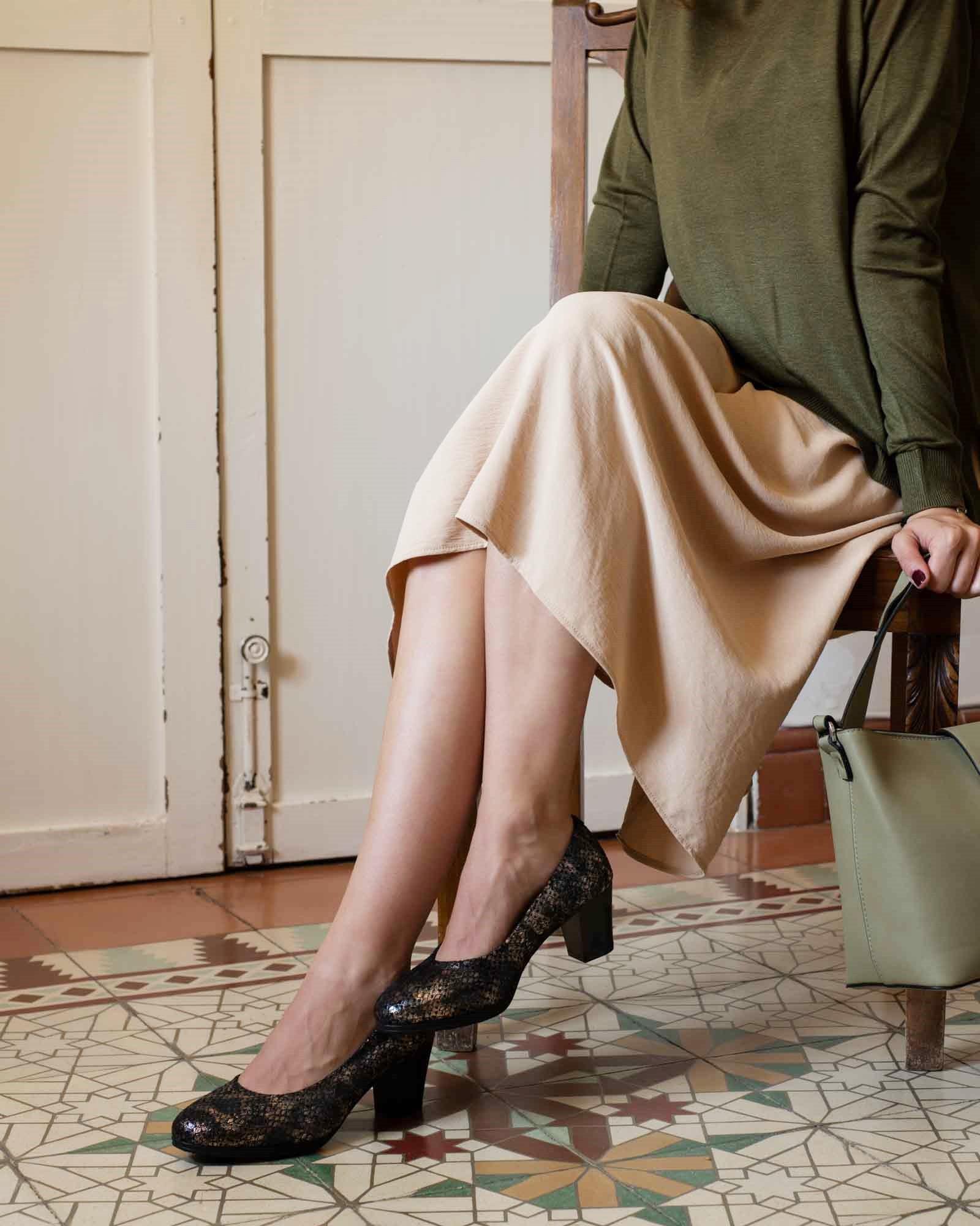 Piernas de mujer con vestido marrón y zapatos negros, con baldosas marrones españoles