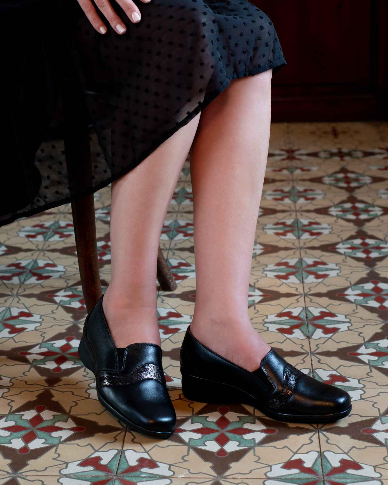 Piernas de mujer con vestido y zapatos negros, con baldosas marrones españoles