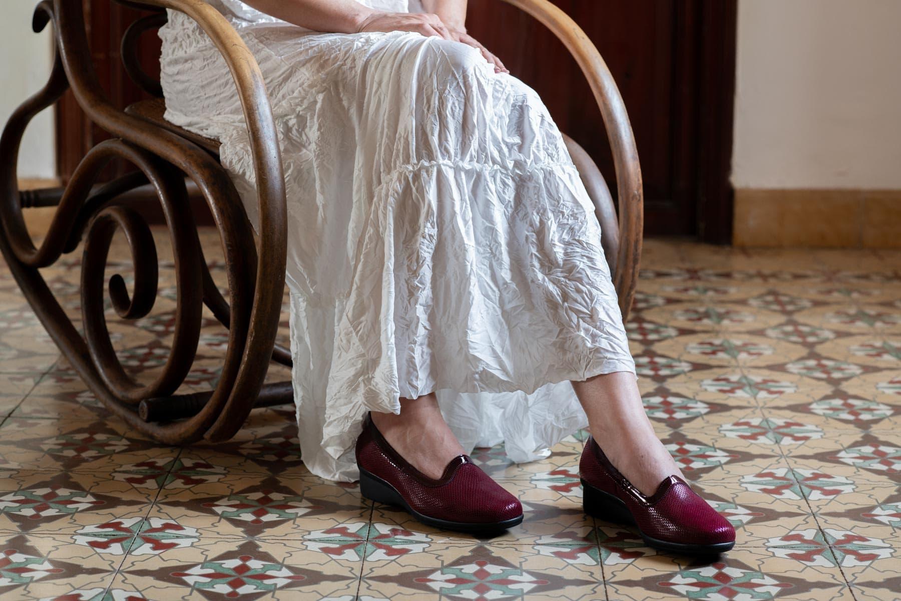 Mujer sobre mecedora y falda blanca en el salón