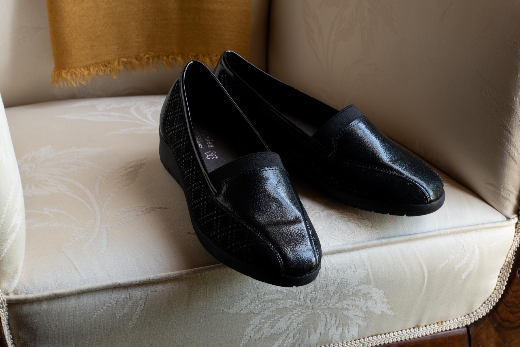 Zapatos negros sobre calzadora antigua con cojín mostaza