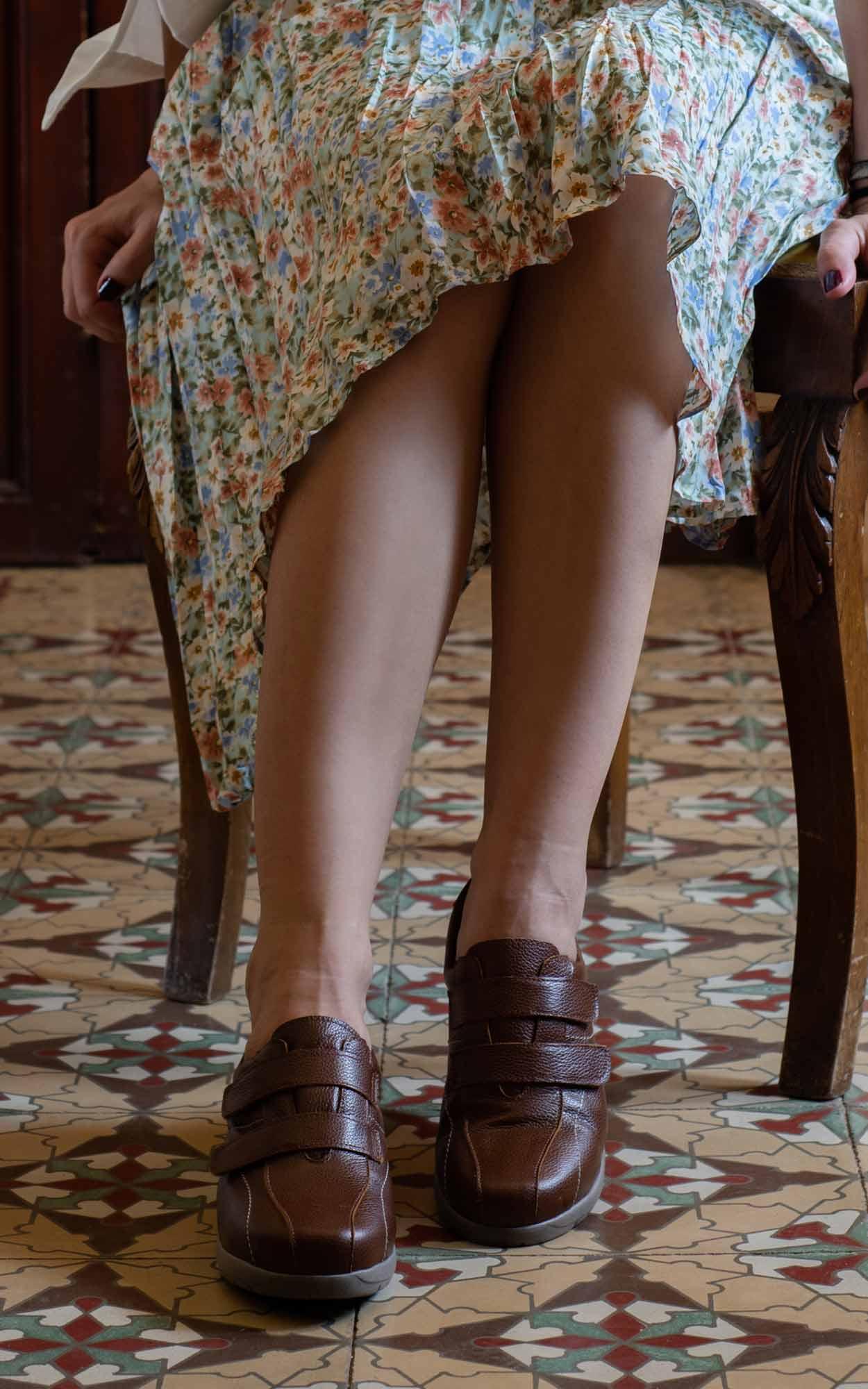 Mujer sentada en una silla antigua con zapatos marrónes y vestido con flores y con baldosas españoles.