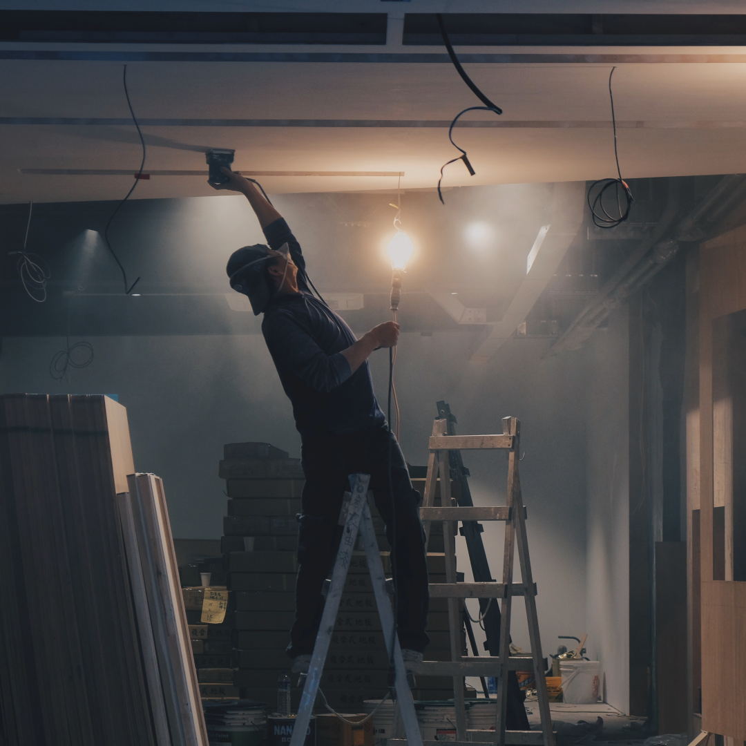 Construction worker fixing ceiling and bulb on a ladder