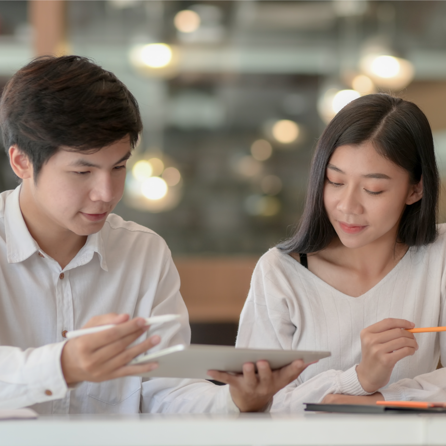 Asian Couple Working In a cafe holding orange pen
